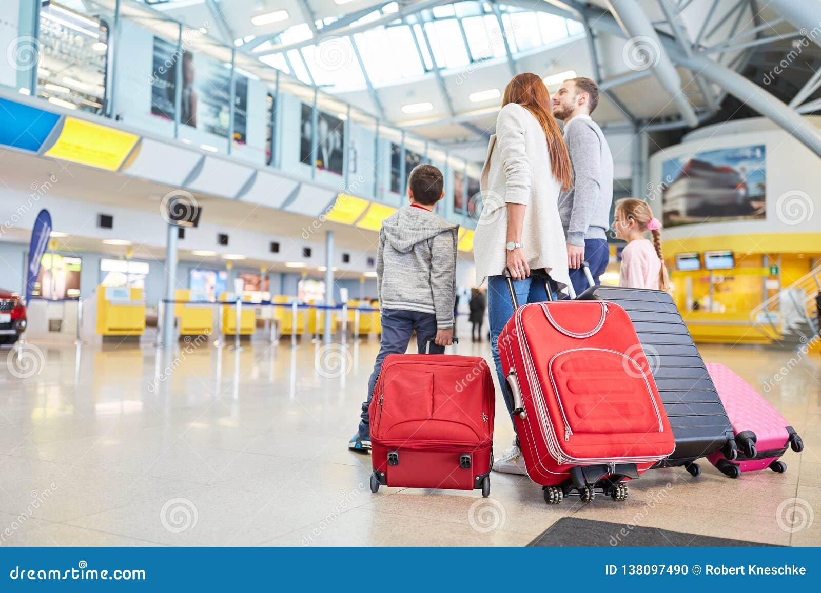Familjen och barn i flygplatsen väntar på avvikelse