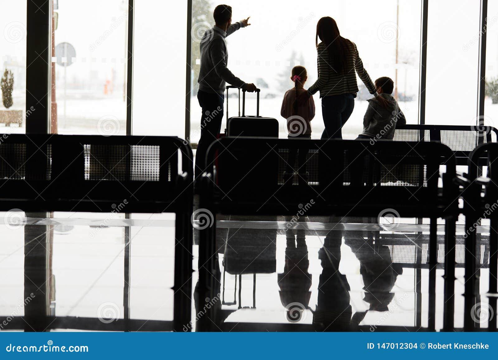 Familjen och barn väntar på flygplatsterminalen