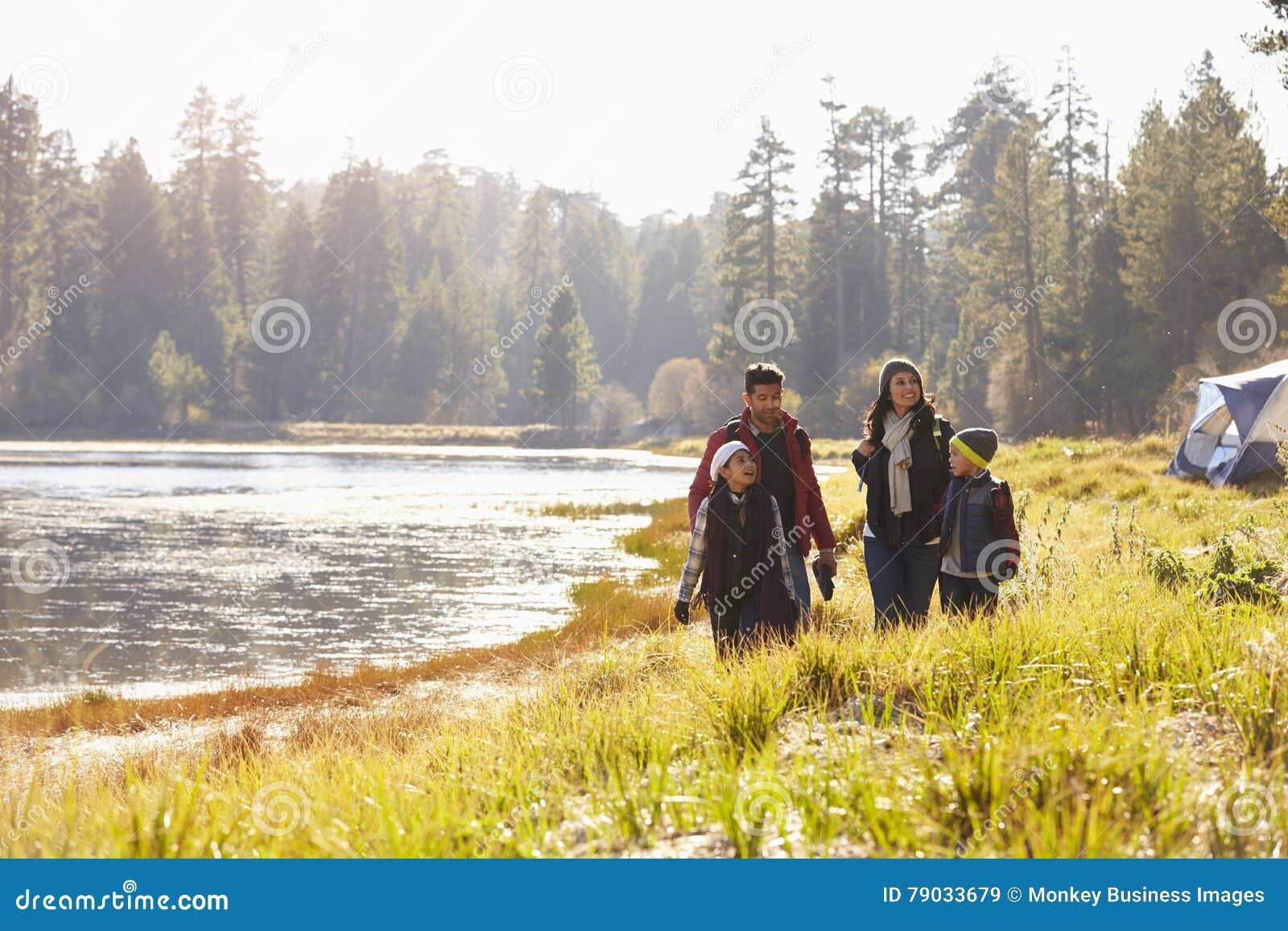 Familjen på campa tur går nära sjön som ser de