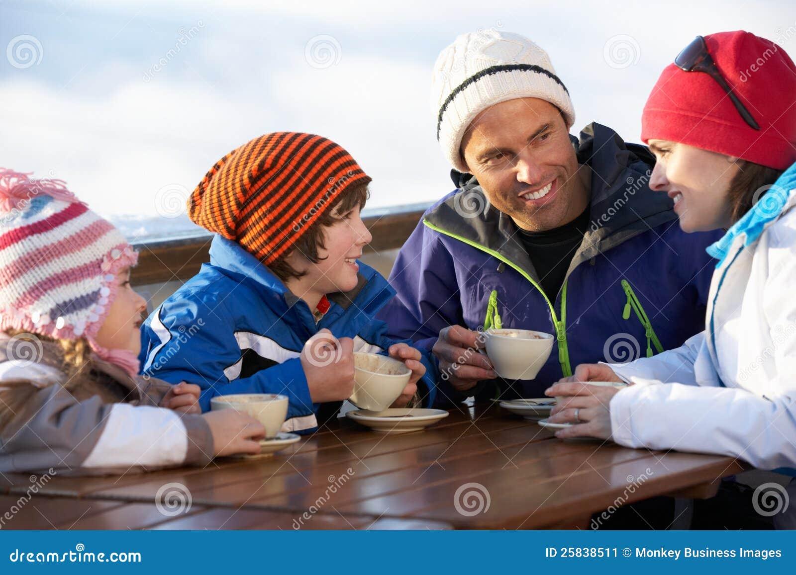 Familjen som tycker om den varma drinken i Cafe på, skidar semesterorten
