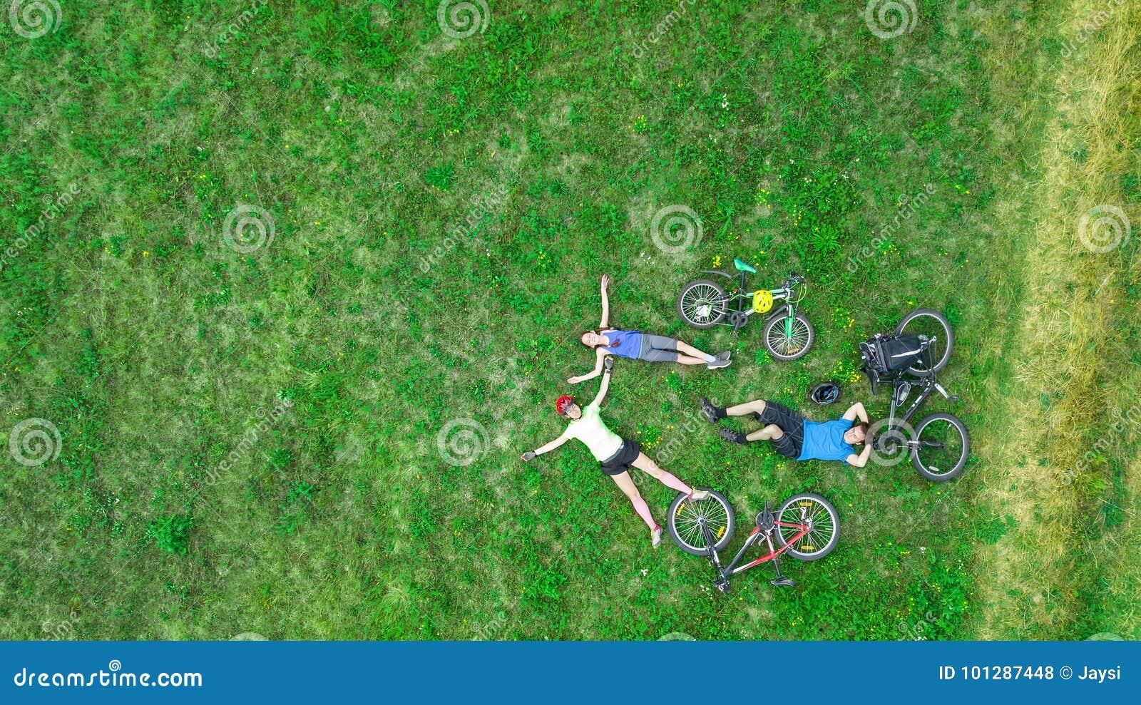 Familjen som utomhus cyklar på flyg- sikt för cyklar från över, lyckliga aktiva föräldrar med barnet, har gyckel och kopplar av p