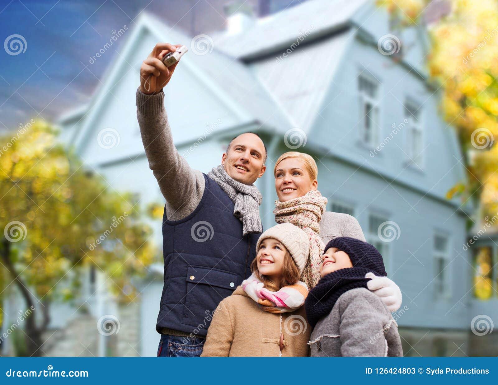 Familjen tar höstselfie vid kameran över hus