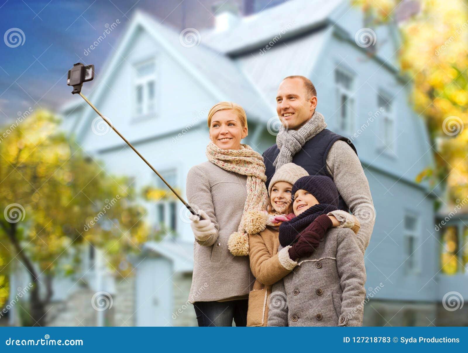 Familjen tar höstselfie vid mobiltelefonen över hus