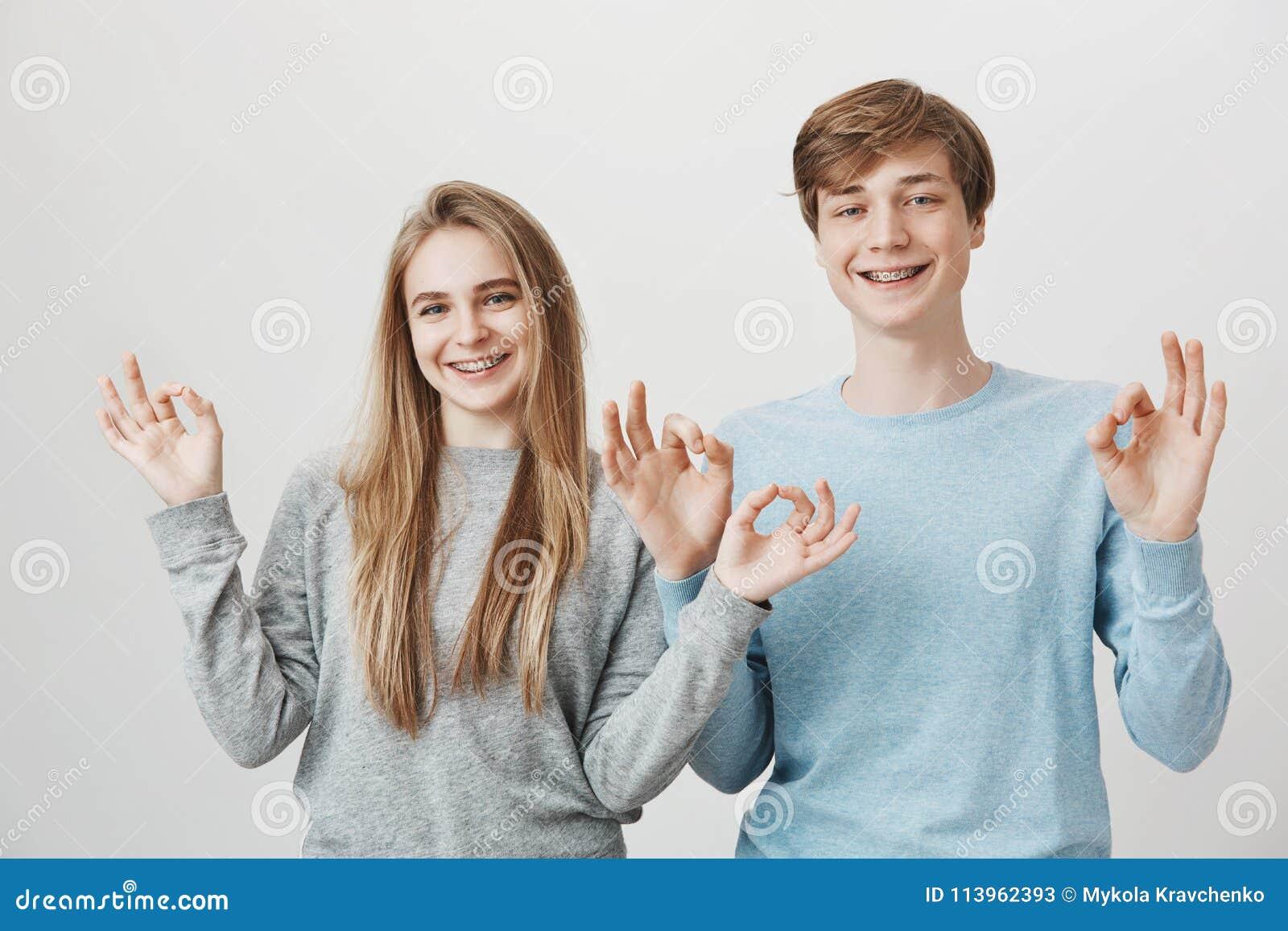 Familjenhet ser som denna Charmigt vänligt syskon som i huvudsak ler, står near och ok visar gest med