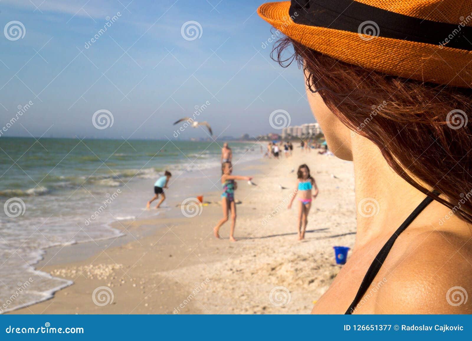 Familjferie för sandig strand, hållande ögonen på barn för nätt kvinnadetalj som spelar på solen i swimwear på den härliga havsst