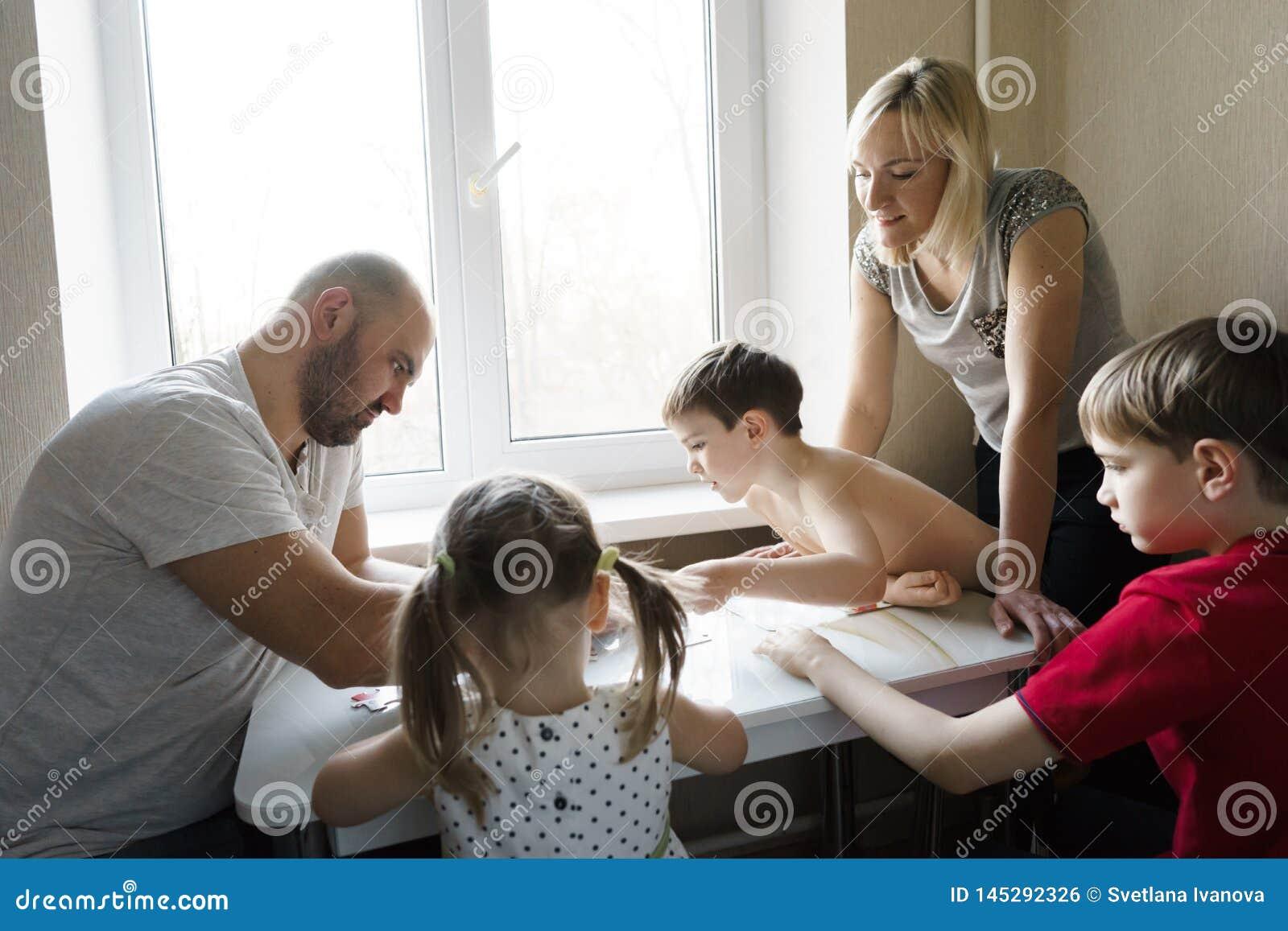 Familjfritid: fader, moder, söner och lekar för dotterlekbräde tillsammans