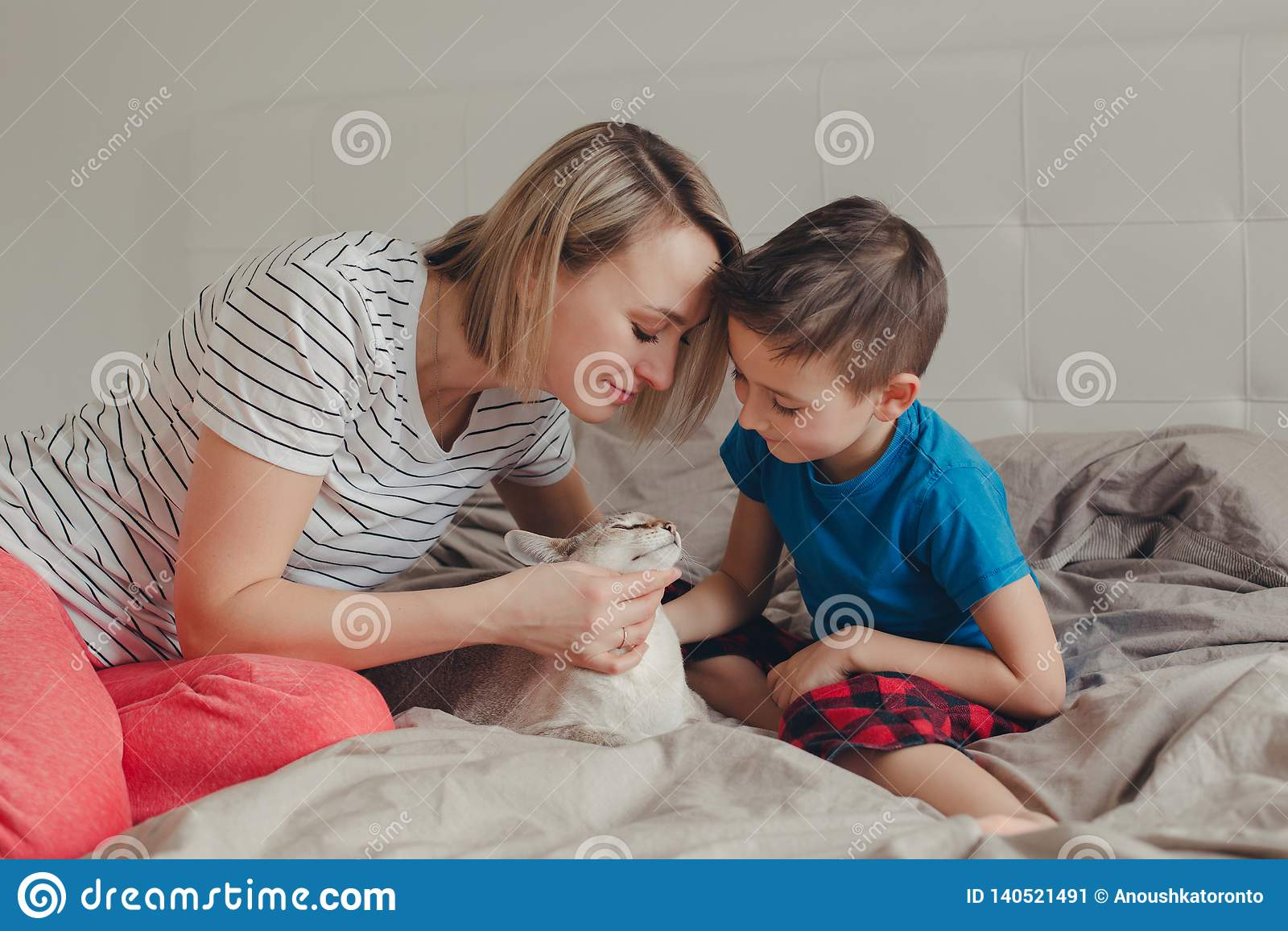 Familjmoder och son som sitter på säng i det hemmastadda sovrummet och daltar den orientaliska punkt-färgade katten