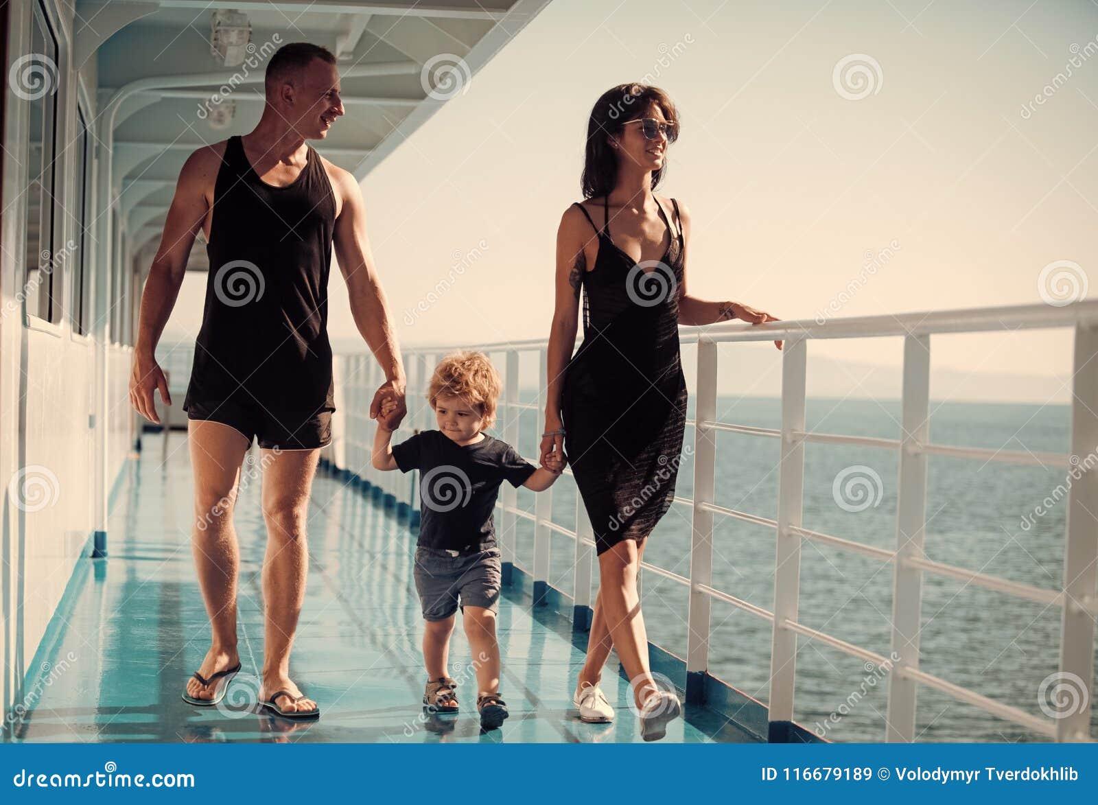 Familjresande på kryssningskeppet på solig dag Familj med den gulliga sonen på sommarsemester Familjen vilar begrepp fader