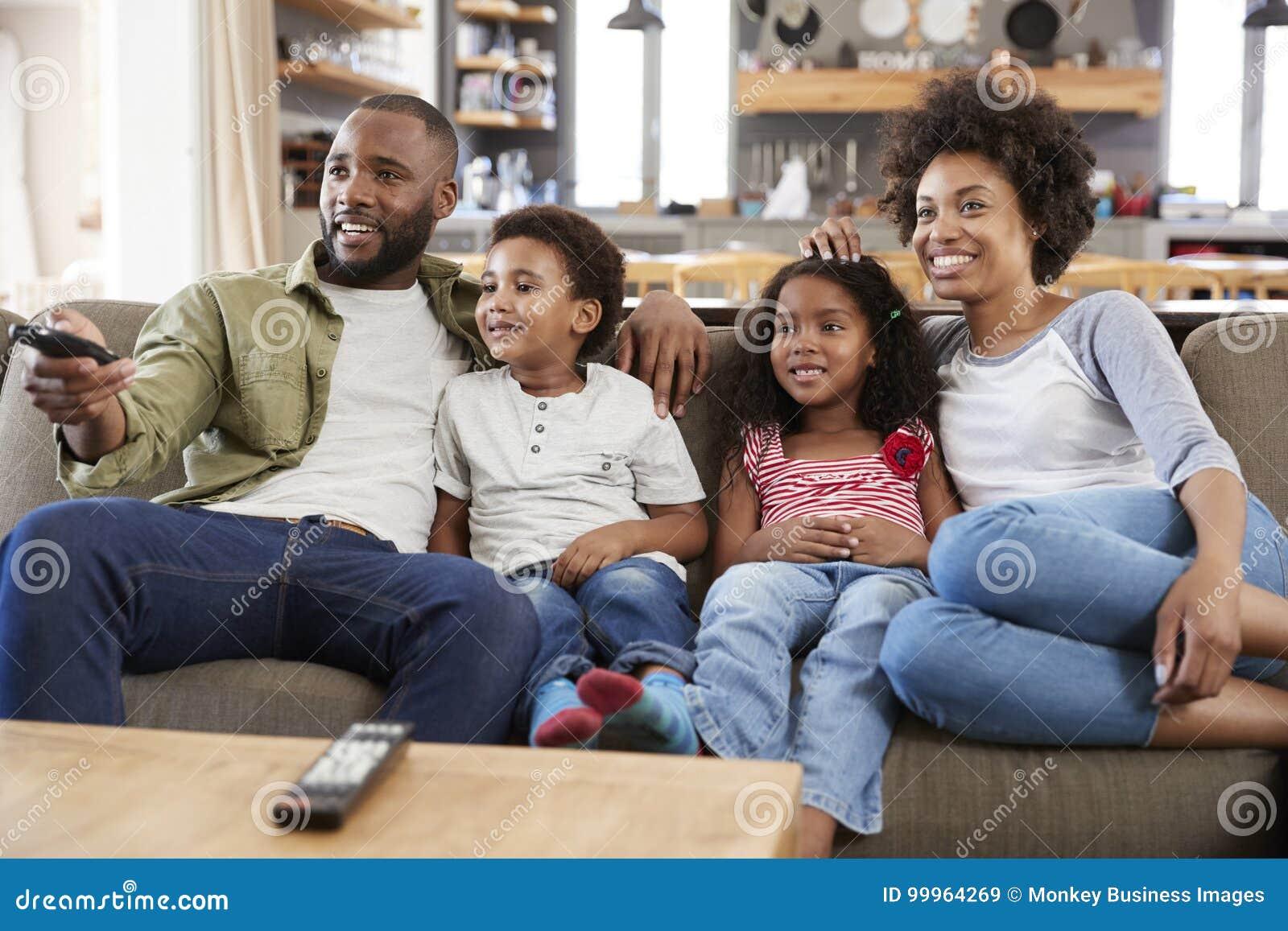 Familjsammanträde på Sofa In Open Plan Lounge hållande ögonen på television