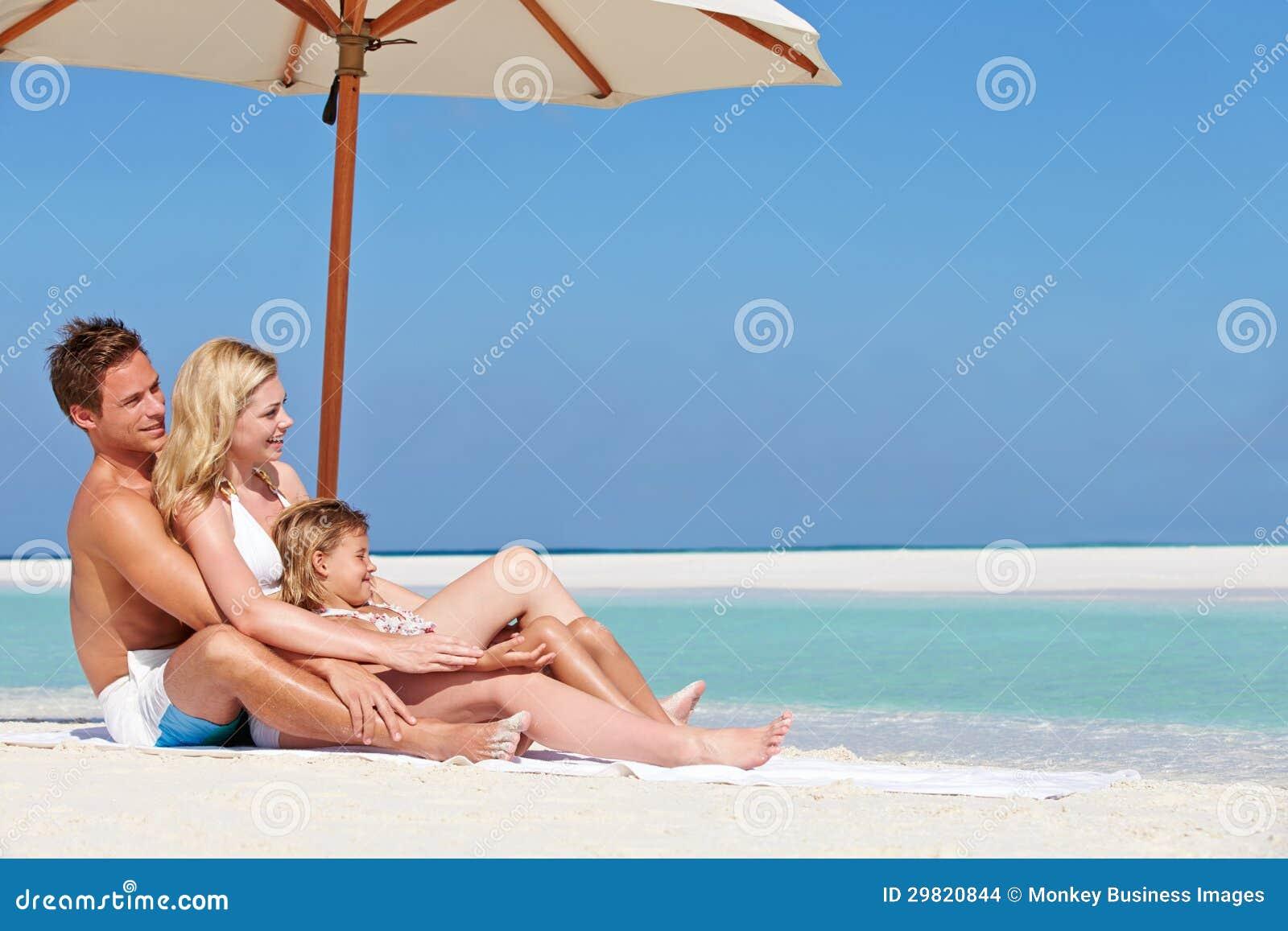 Familjsammanträde under paraplyet på strandferie
