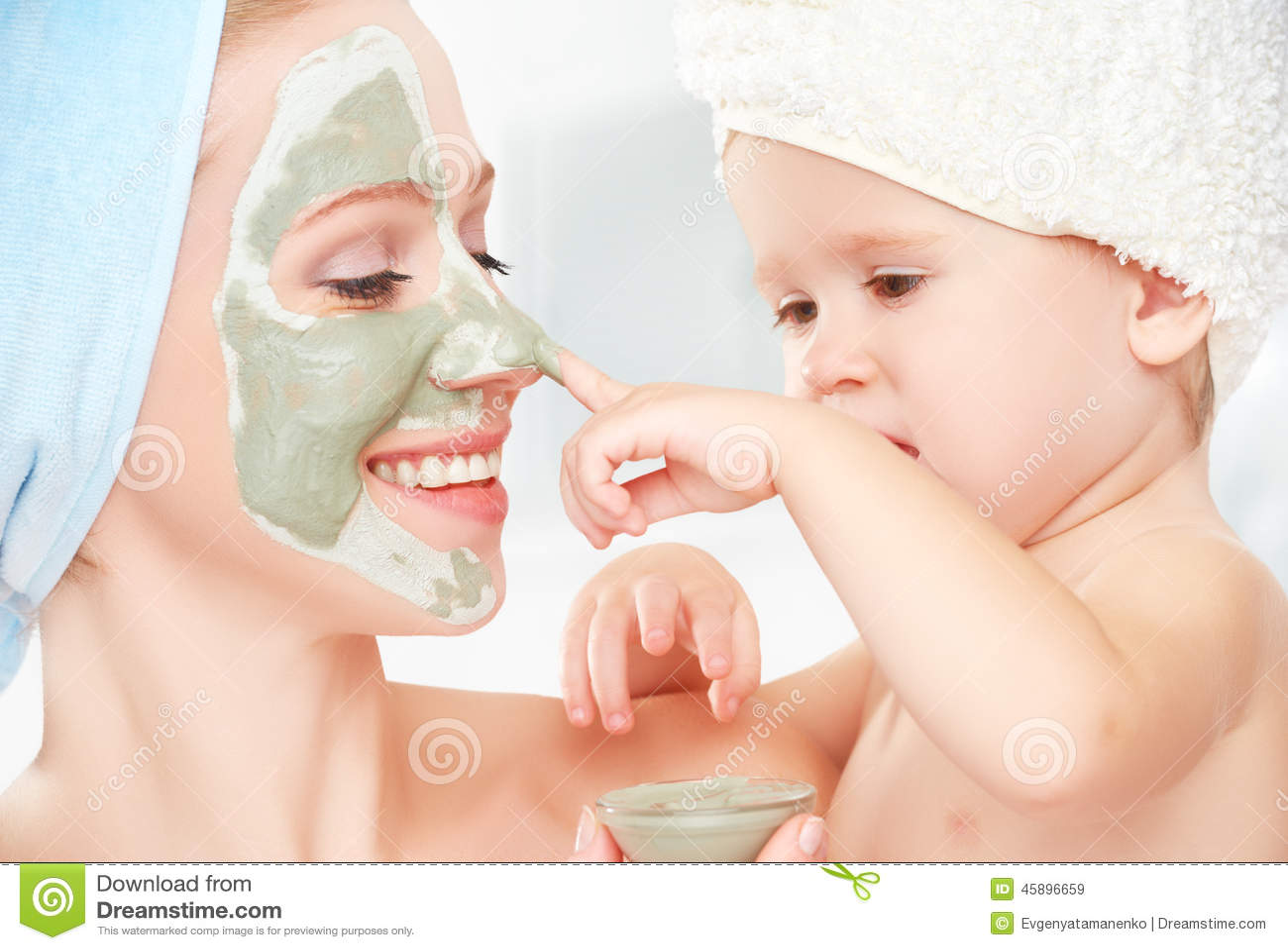 Familjskönhetbehandling i badrummet modern och dottern behandla som ett barn flickan gör en maskering för framsida att flå