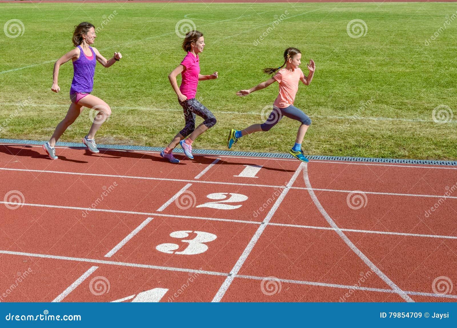 Familjsport, moder och ungar som kör på stadionspår, utbildning och barnkondition