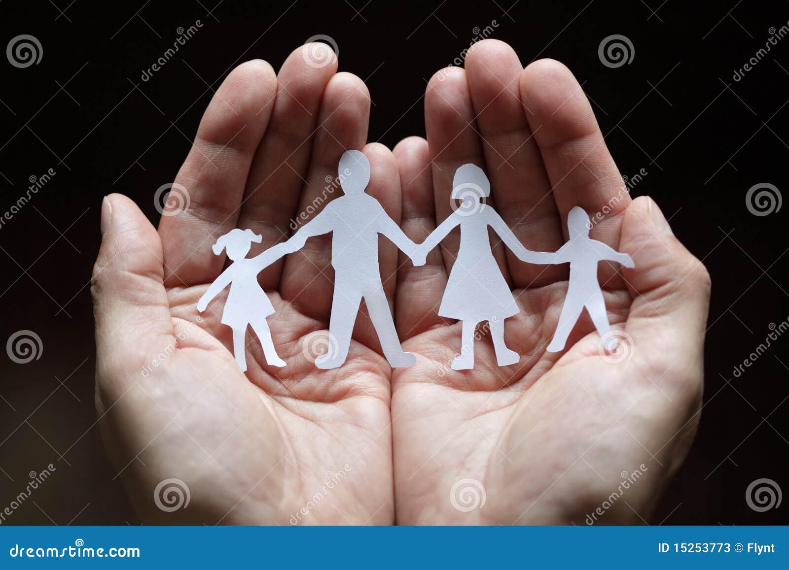 Famille à chaînes de papier protégée dans des mains évasées