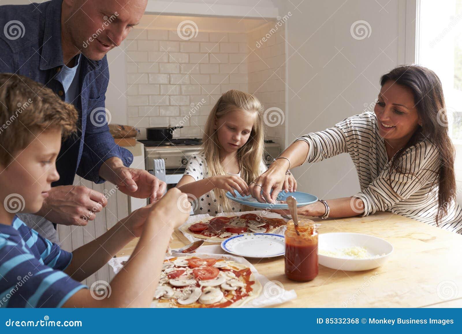 Famille à la maison dans la cuisine faisant des pizzas ensemble