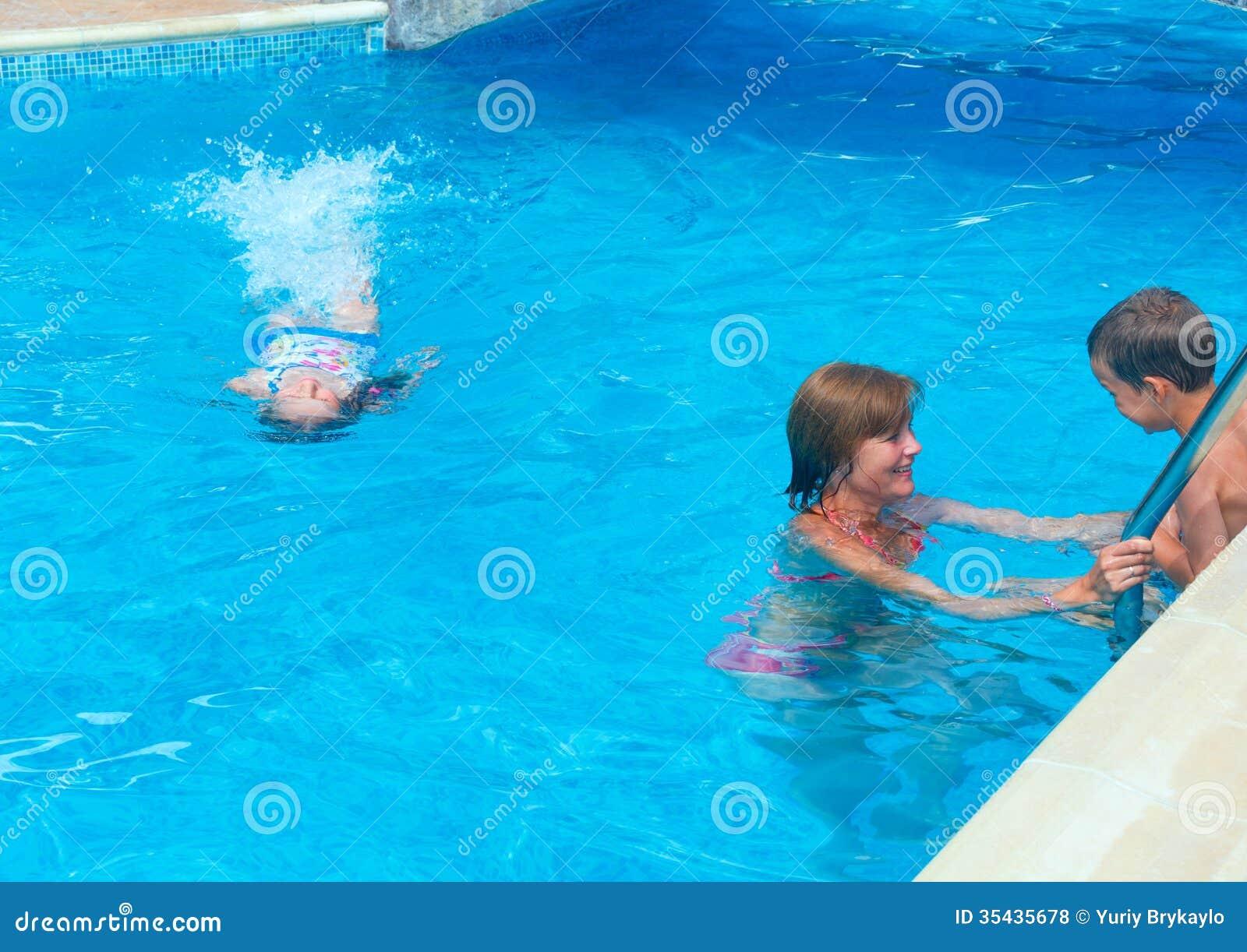 Famille nager dans la piscine photos libres de droits for Piscine pour nager