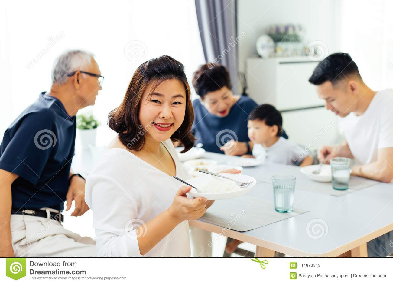 Famille étendu asiatique heureux dînant à la maison complètement de bonheur et de sourires