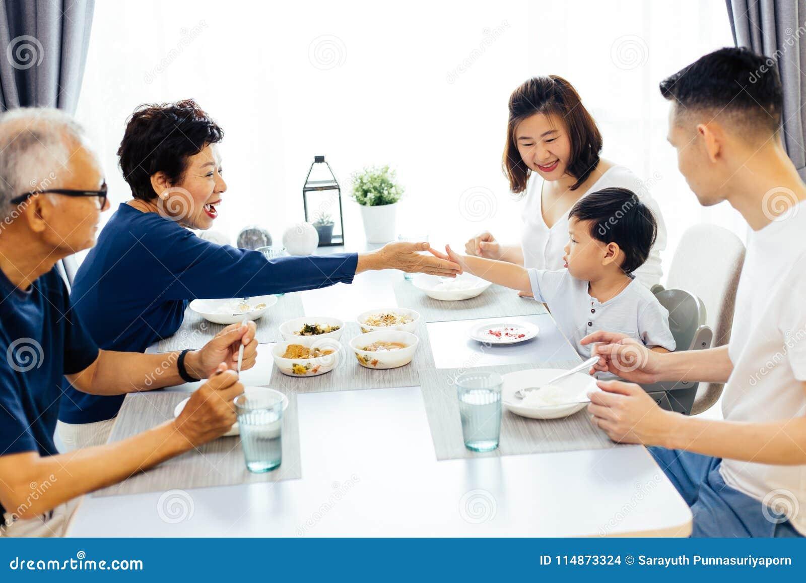 Famille étendu asiatique heureux dînant à la maison complètement de rire et de bonheur