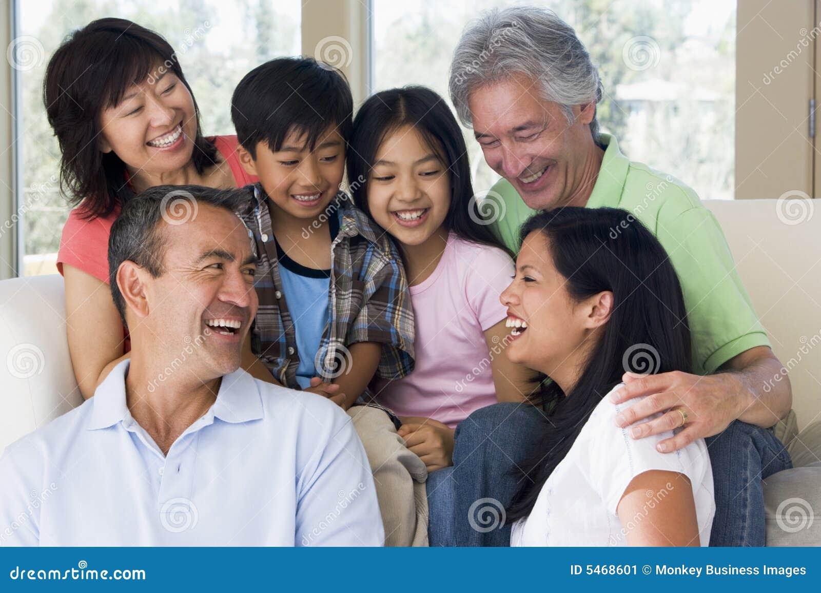 Famille étendu dans le sourire de salle de séjour