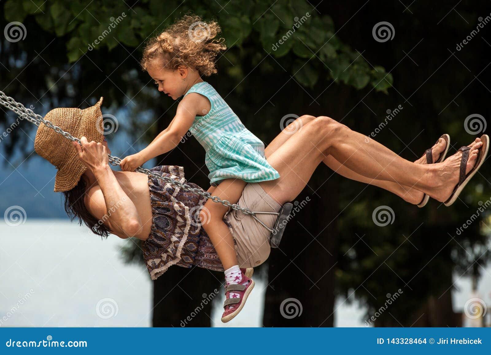 Famille affectueuse heureuse ! Jeune mère et sa fille d enfant balançant sur les oscillations et riant une soirée d été dehors, b