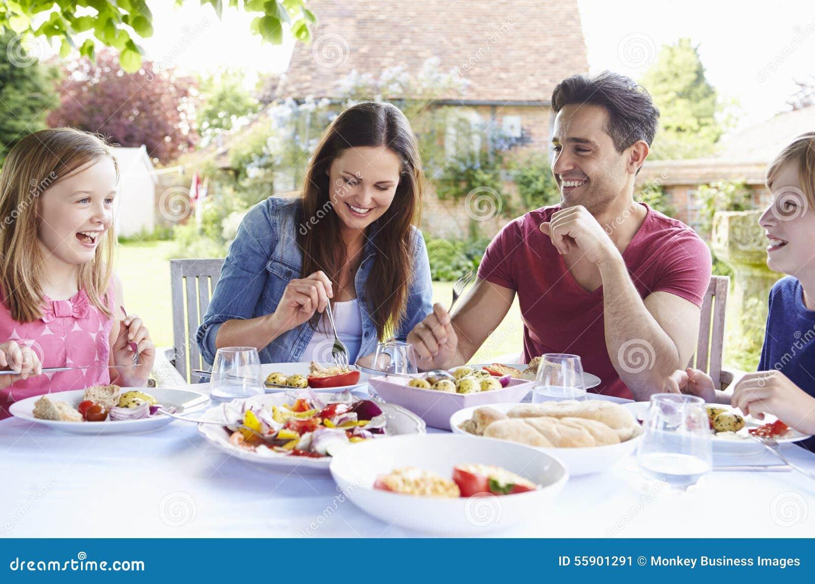 Famille appréciant le repas extérieur ensemble