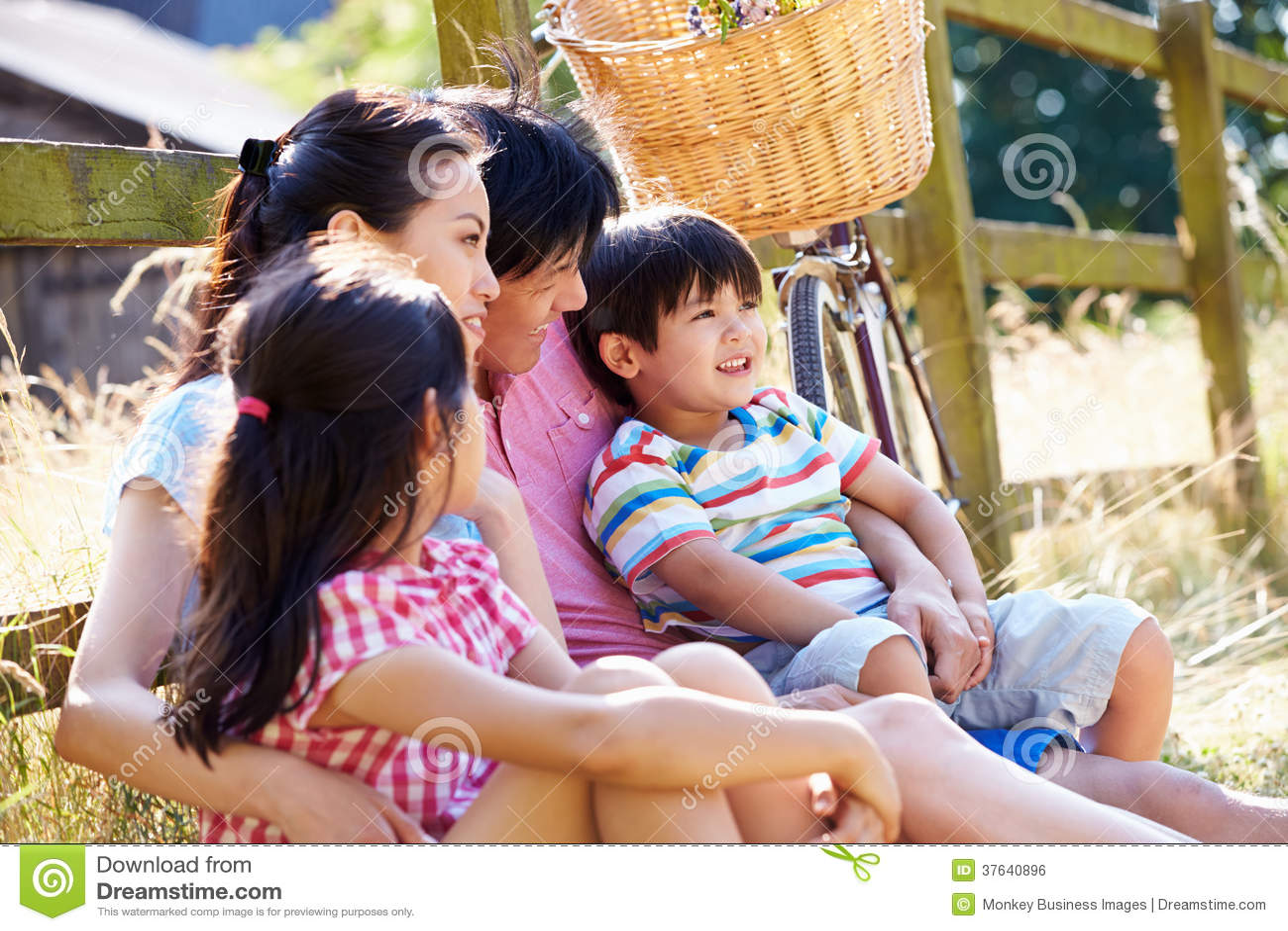Famille asiatique se reposant par le cycle de With Old Fashioned de barrière