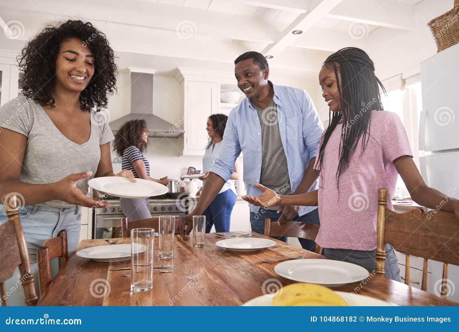 Famille avec des filles adolescentes étendant le Tableau pour le repas dans la cuisine