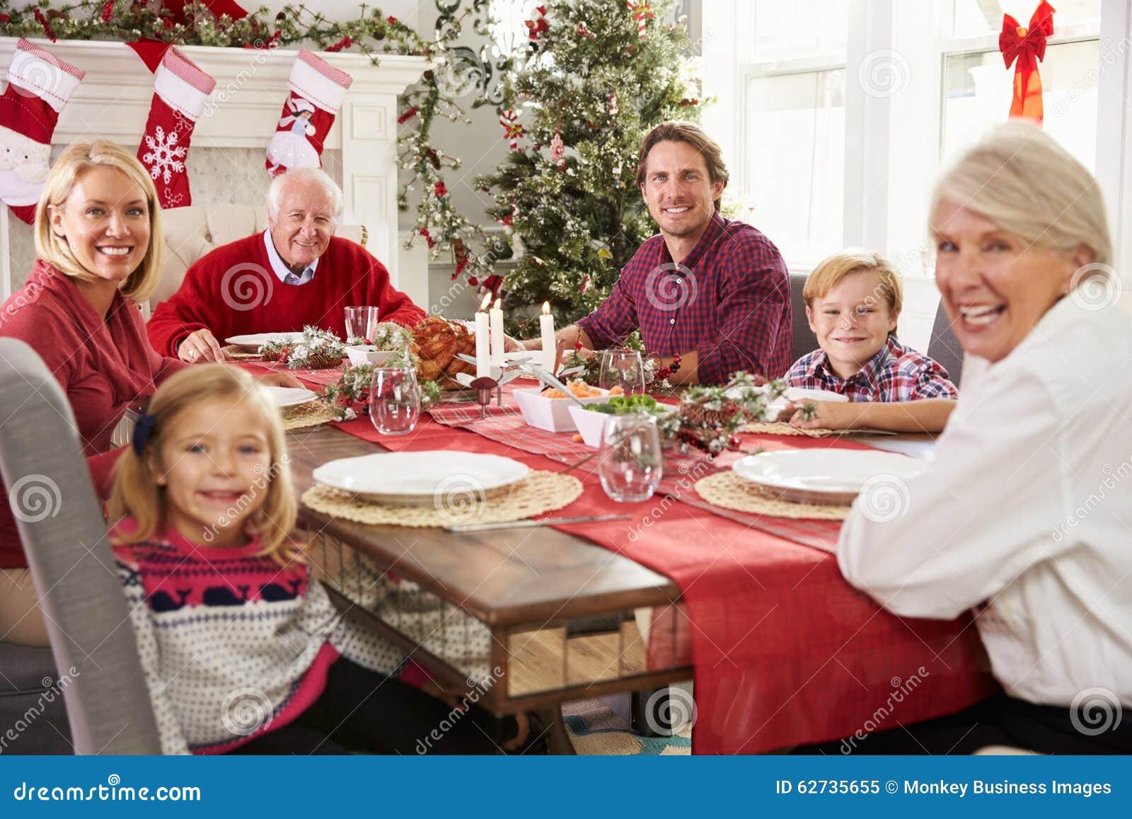 Famille avec des grands-parents appréciant le repas de Noël au Tableau