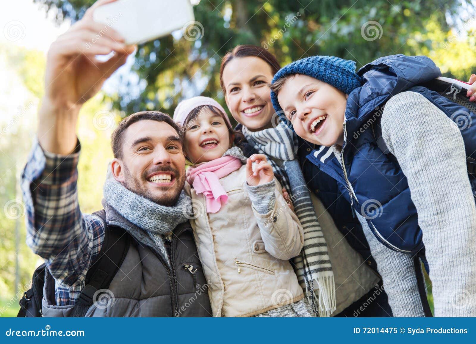 Famille avec des sacs à dos prenant le selfie par le smartphone