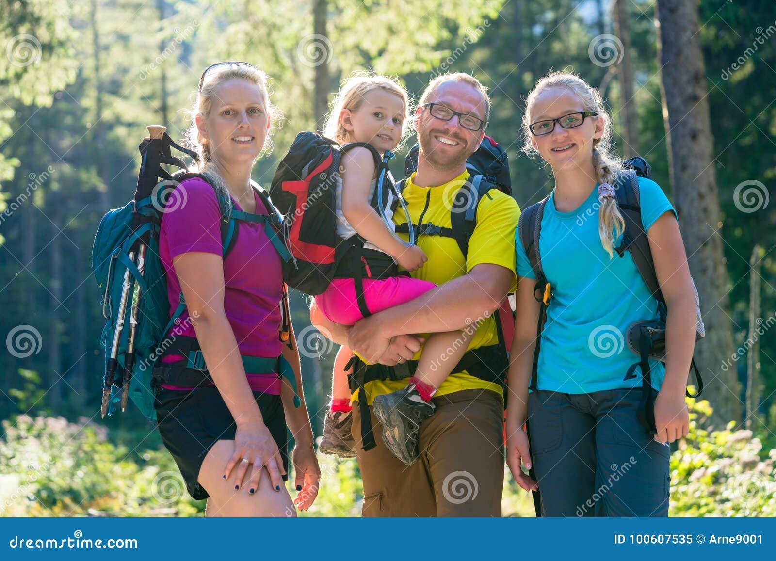 Famille avec deux filles sur la hausse dans les bois