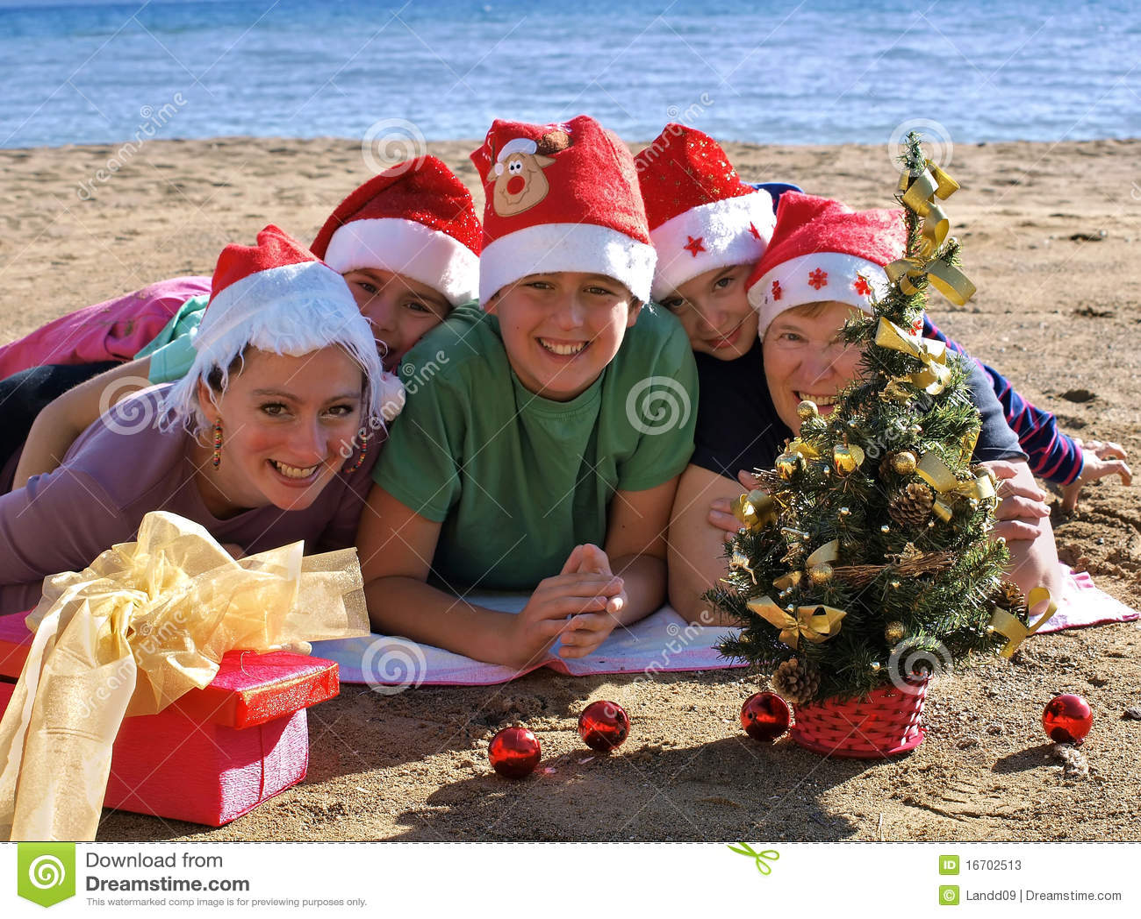 Famille avec le chapeau du père noël sur la plage