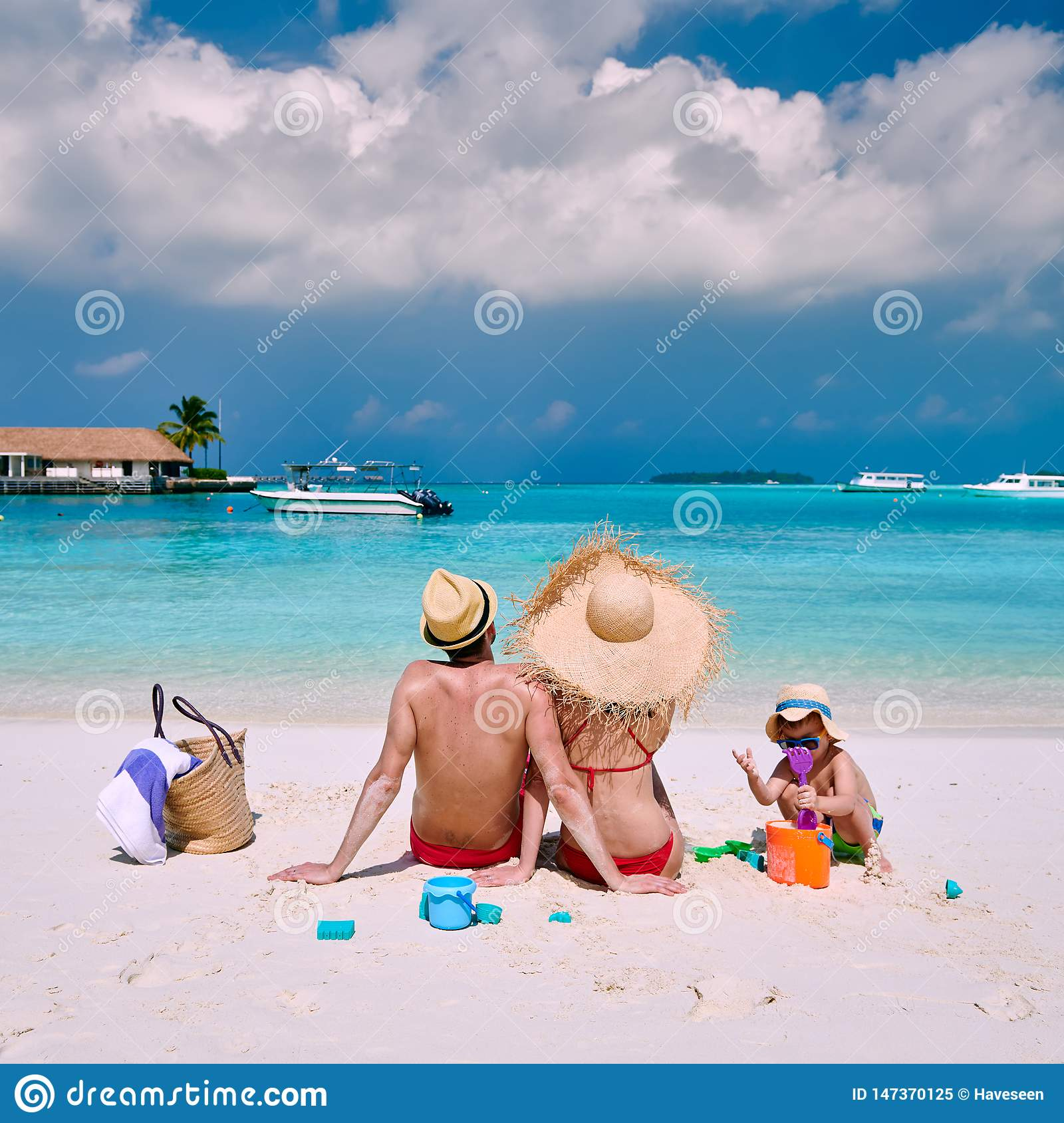 Famille avec le gar?on trois an sur la plage