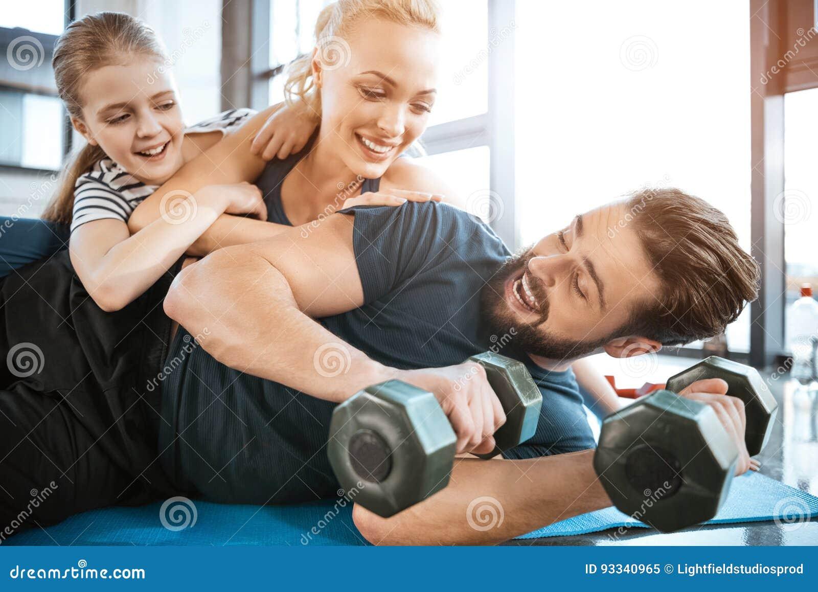 Famille ayant l amusement au gymnase, homme tenant des haltères
