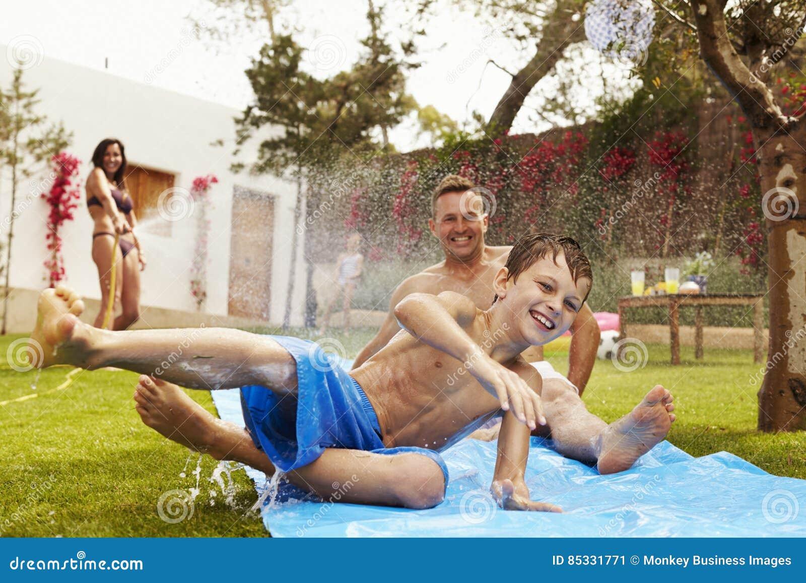 Famille ayant l amusement sur la glissière d eau dans le jardin