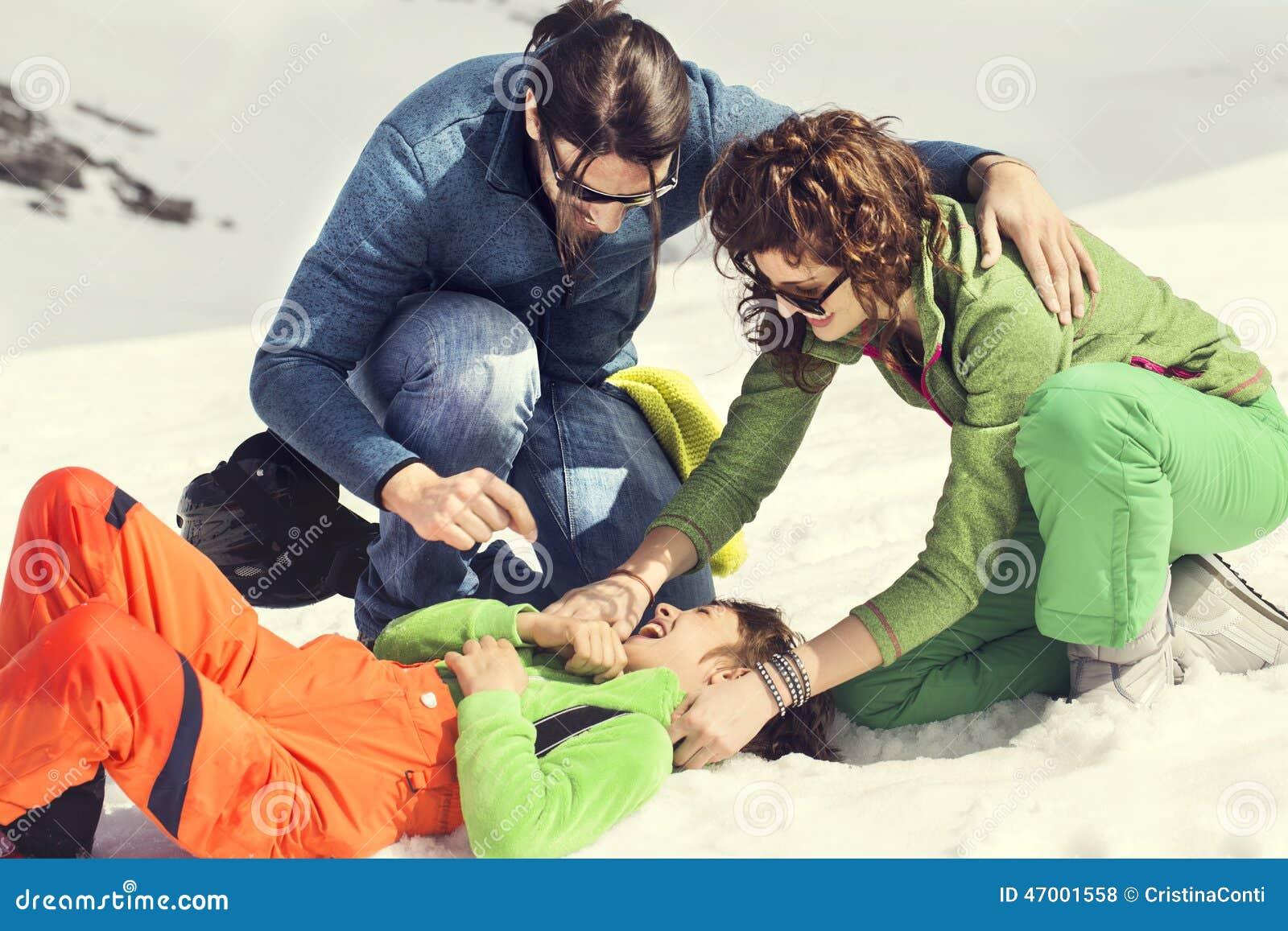 Famille choyant leur fils sur la neige