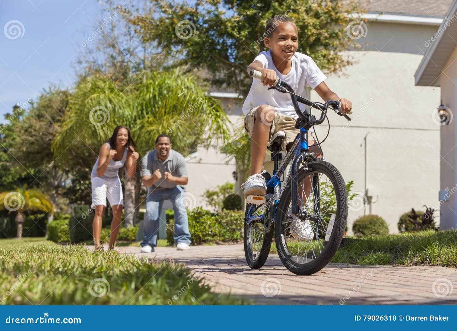 Famille d afro-américain avec le vélo d équitation de garçon et les parents heureux