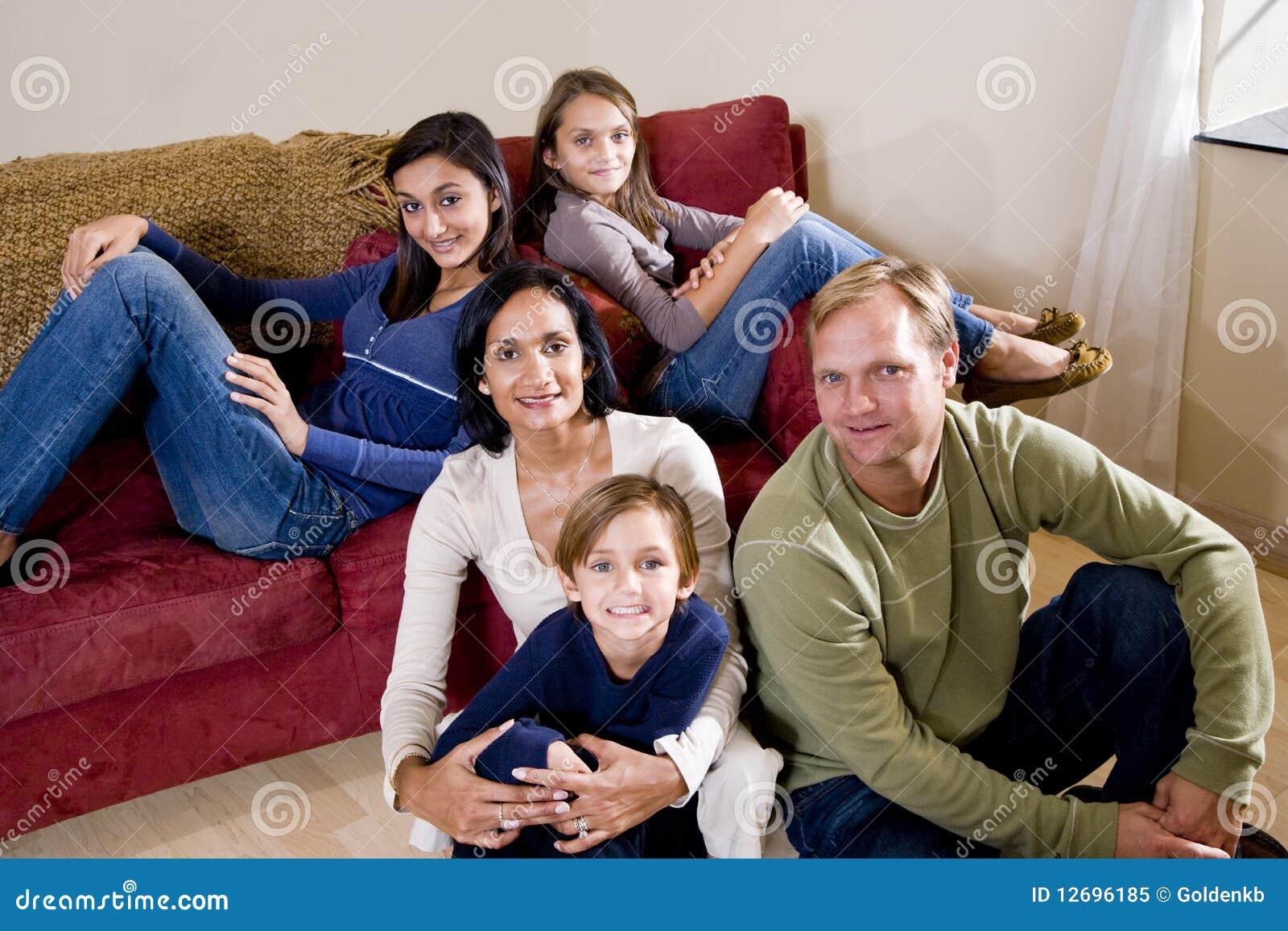 Famille de cinq interraciale détendant à la maison