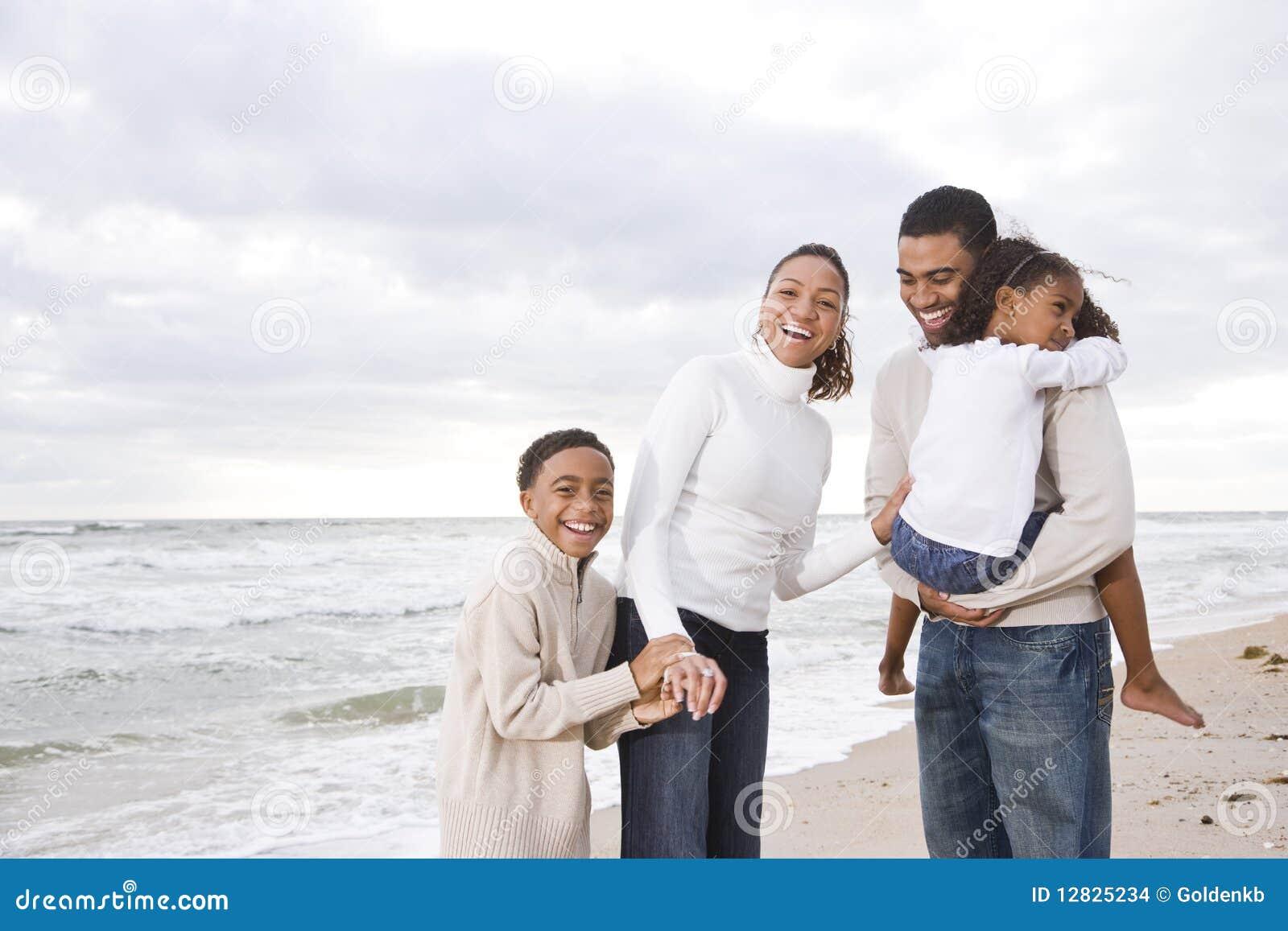 Famille de quatre afro-américaine heureuse sur la plage