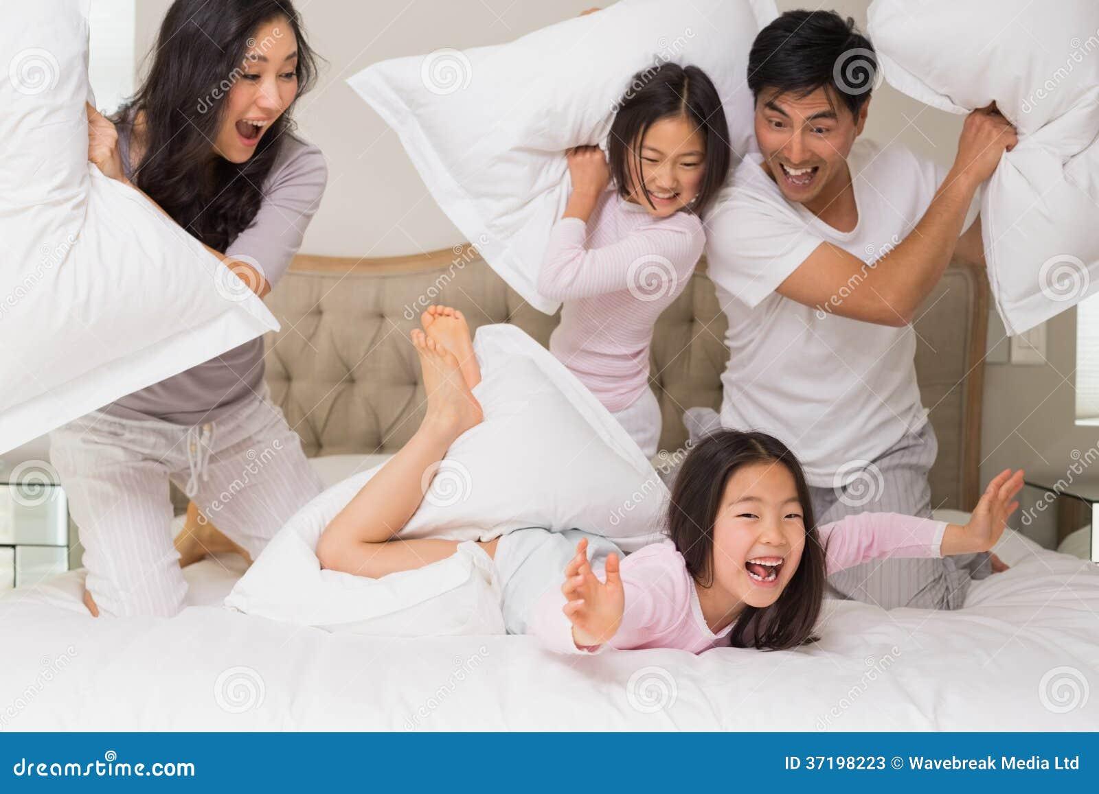 Famille de quatre ayant le combat d oreiller sur le lit