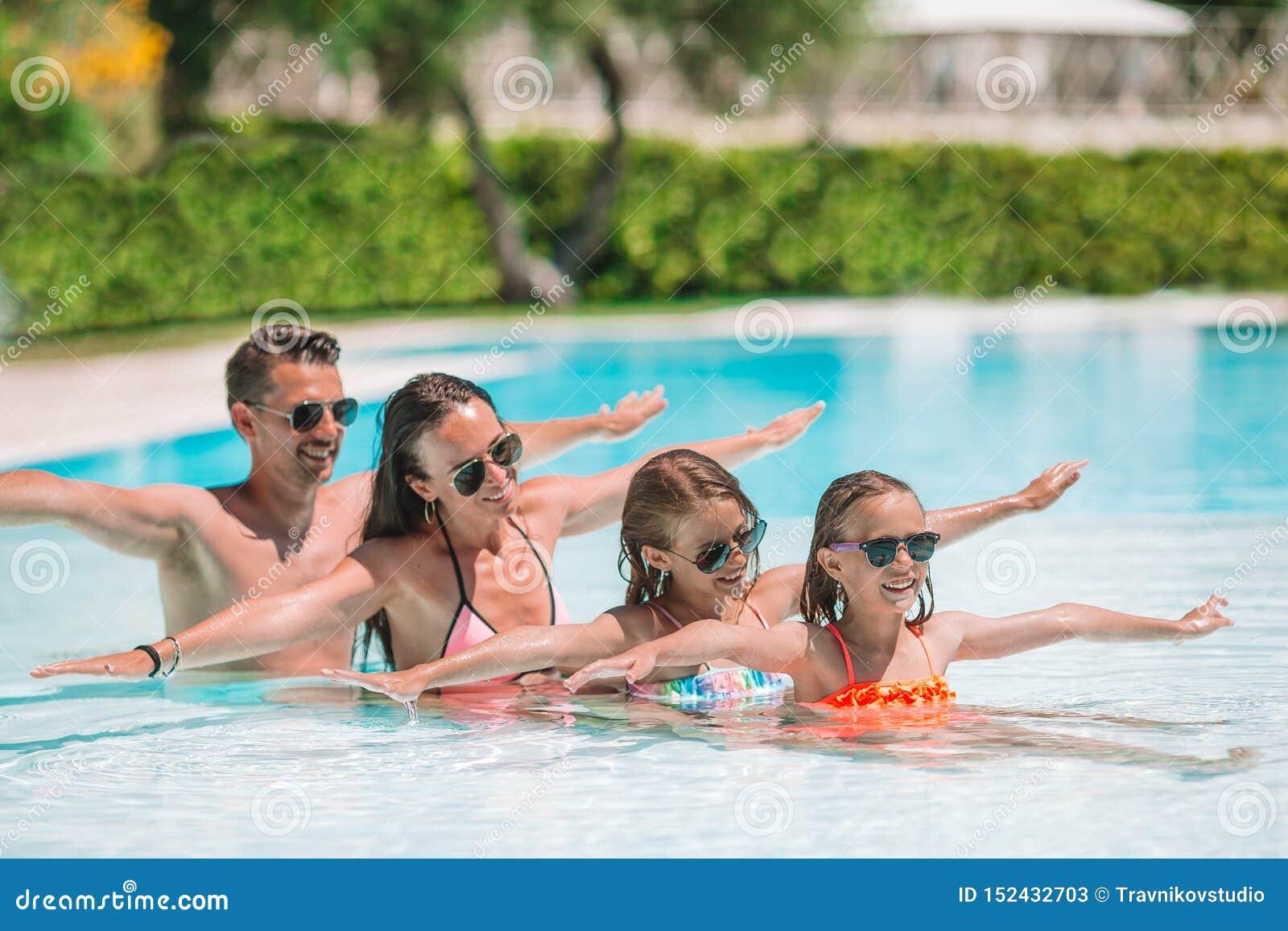 Famille de quatre heureuse dans la piscine d extérieur