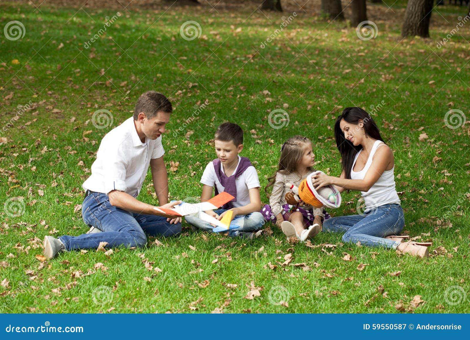Famille de quatre heureuse, se reposant en parc d automne