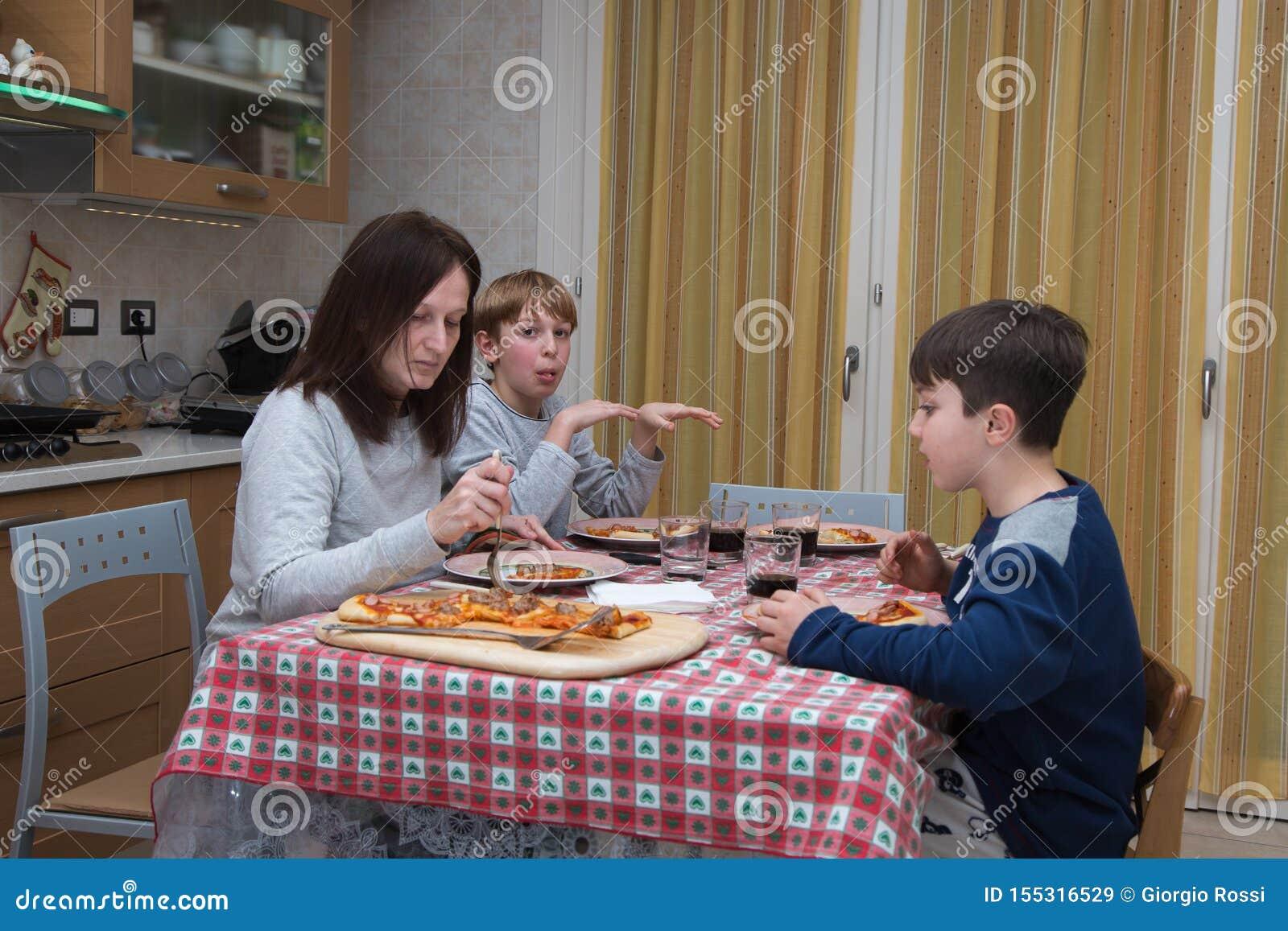 Famille De Quatre Personnes Mangeant De La Pizza Sur La Table De