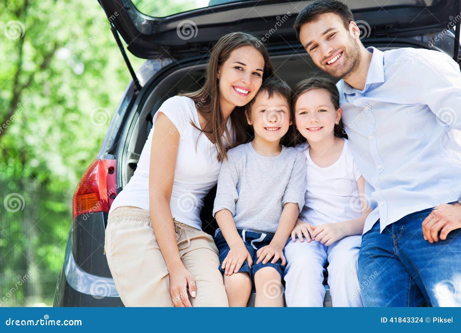 Famille de quatre se reposant dans le tronc de voiture