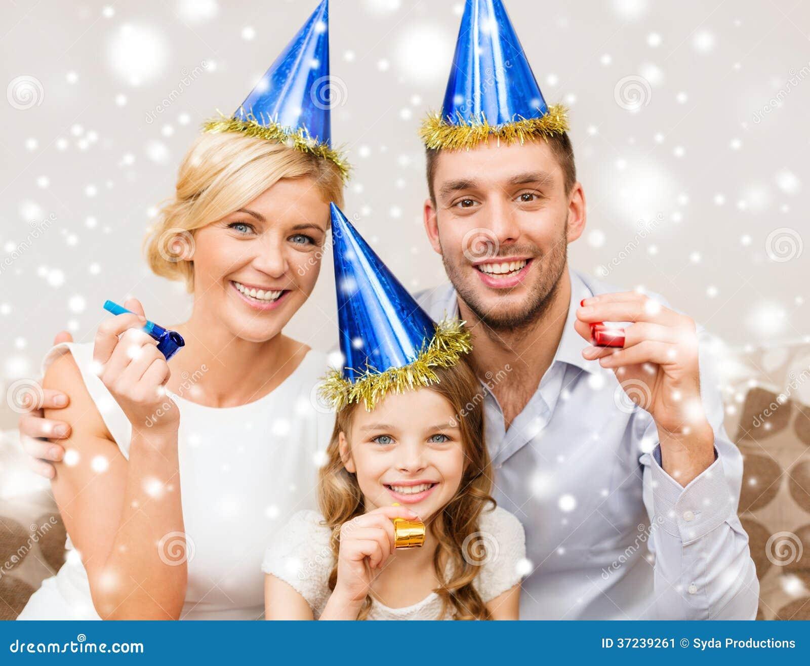 Famille de sourire dans des chapeaux bleus soufflant des klaxons de faveur