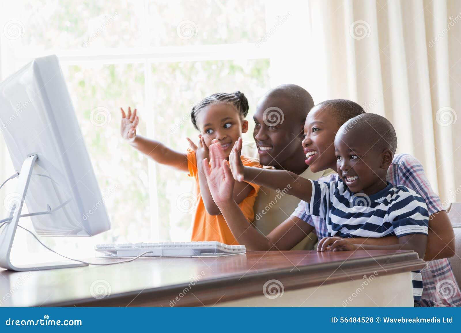 Famille de sourire heureuse causant avec l ordinateur ensemble