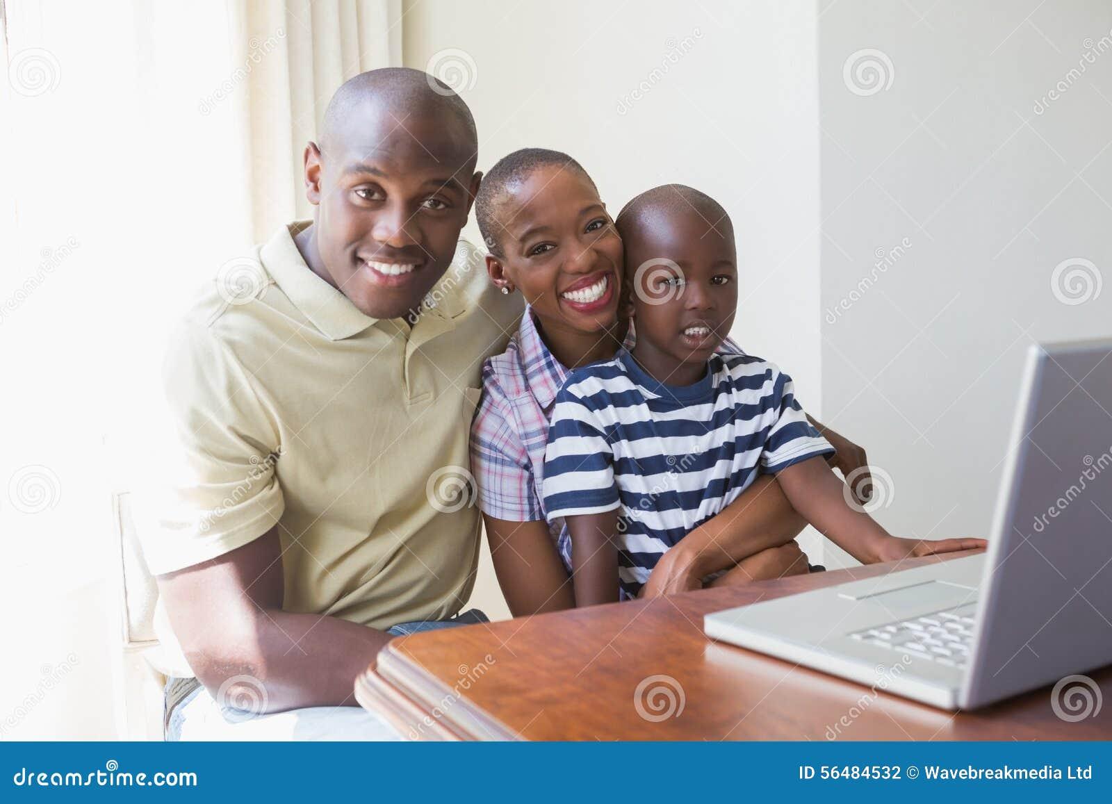 Famille de sourire heureuse utilisant l ordinateur portable