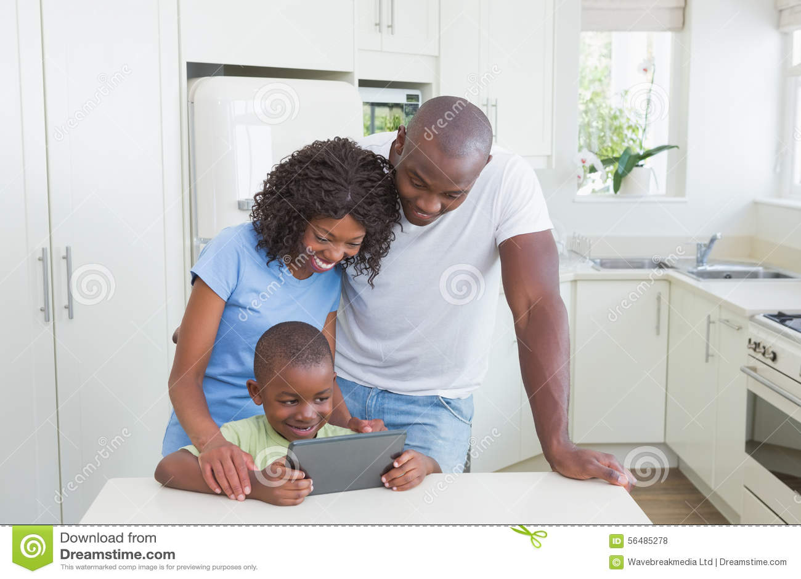 Famille de sourire heureuse utilisant le comprimé numérique