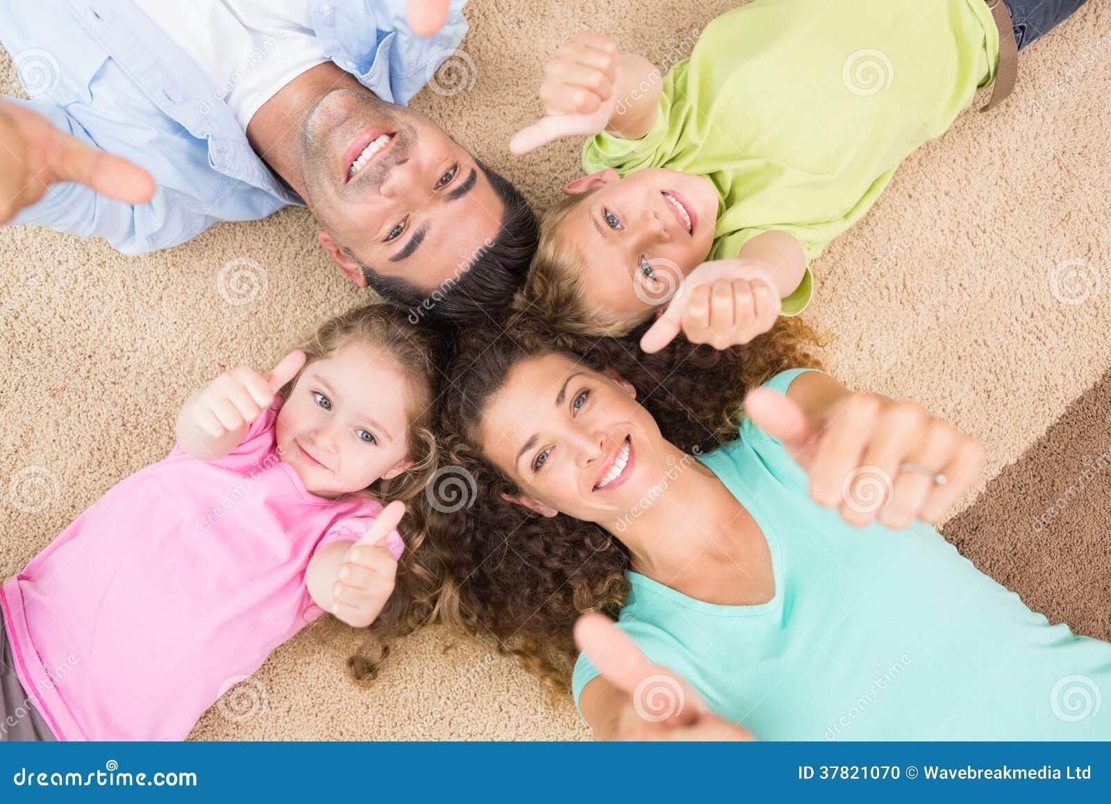 Famille de sourire se trouvant sur la couverture en cercle montrant des pouces