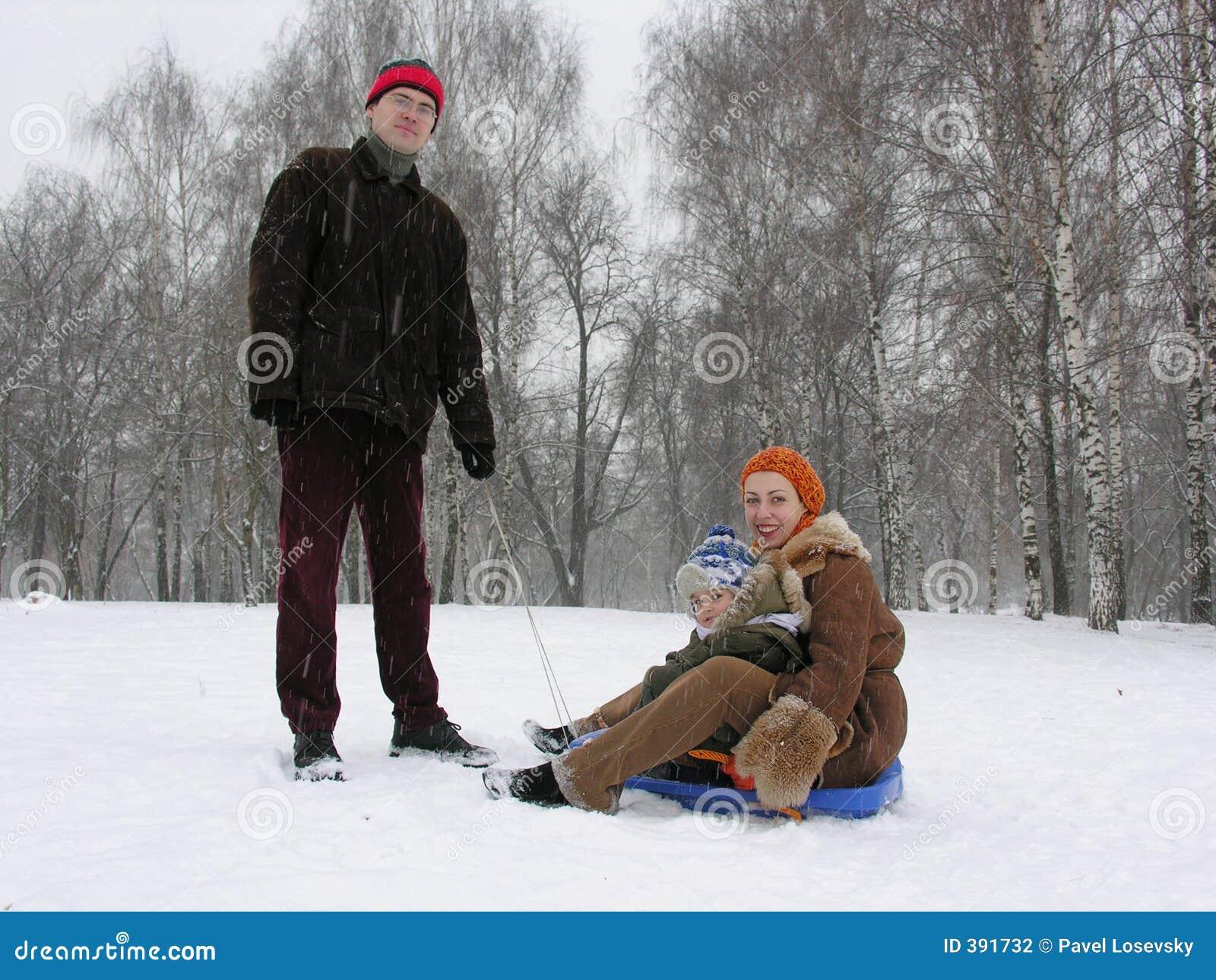 Famille de trois avec le traîneau. l hiver