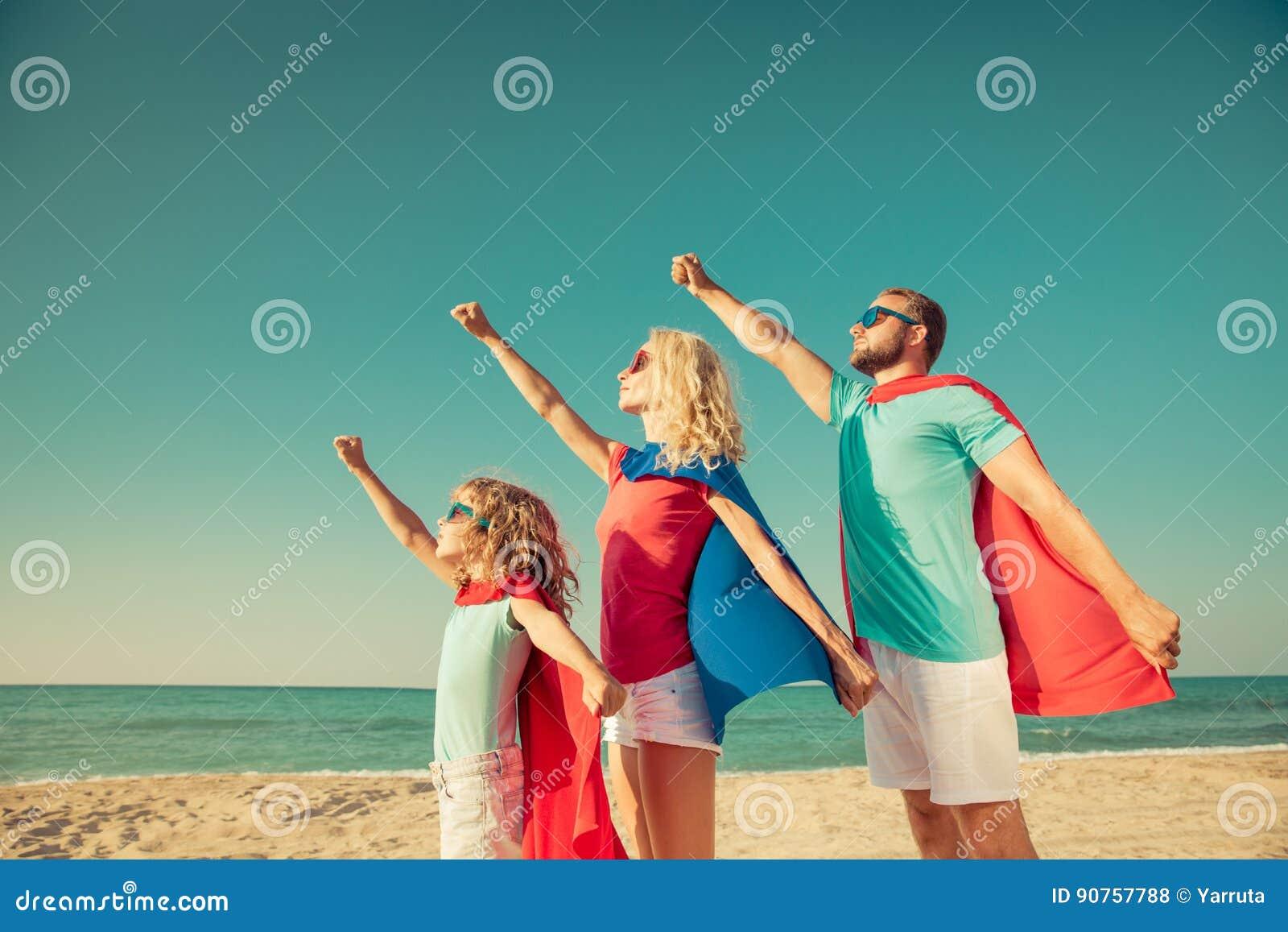 Famille des super héros sur la plage Concept de vacances d été