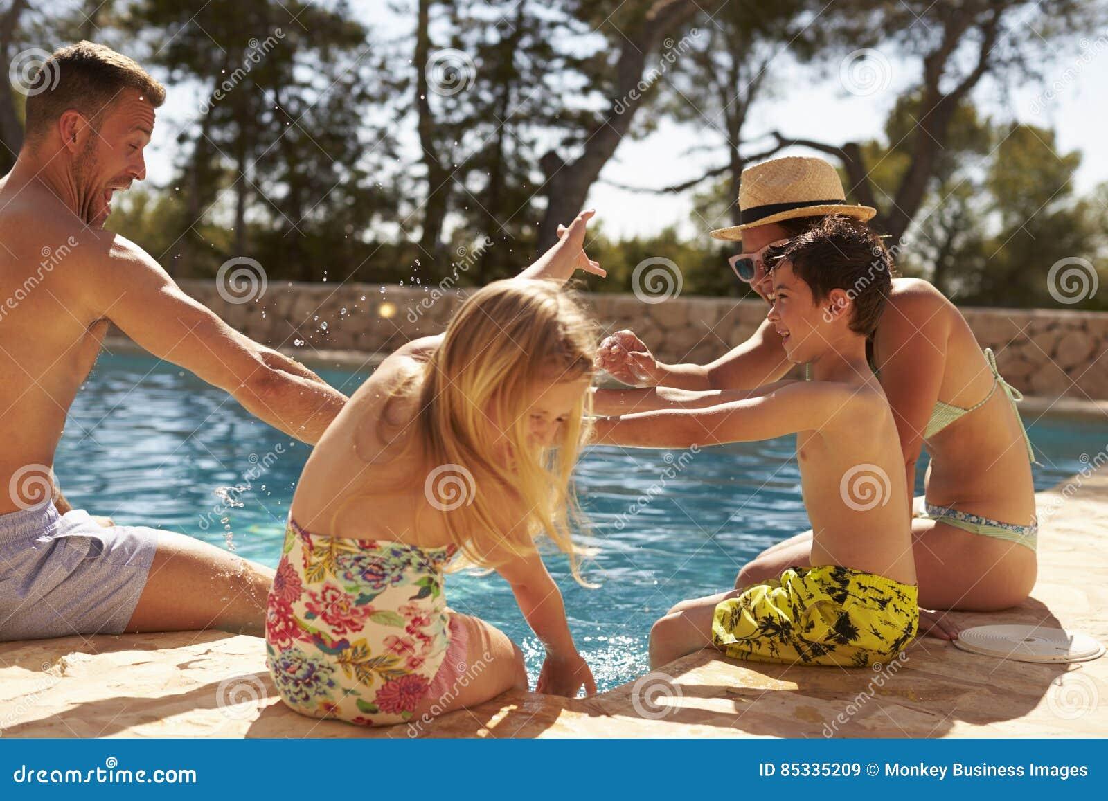 Famille des vacances ayant l amusement par la piscine extérieure